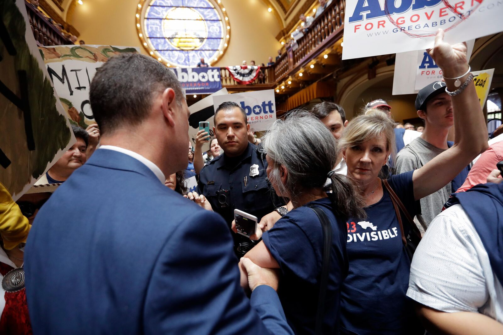 Protesters are led out of an event where Texas Gov. Greg Abbott announced his bid for re-election, Friday, July 14, 2017, in San Antonio. (AP Photo/Eric Gay)