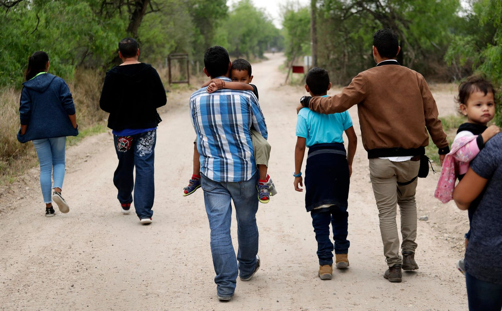 FILE - In this March 14, 2019, file photo, a group of migrant families walk from the Rio Grande, the river separating the U.S. and Mexico in Texas, near McAllen, Texas, right before being apprehended by Border Patrol. (AP Photo/Eric Gay, File)