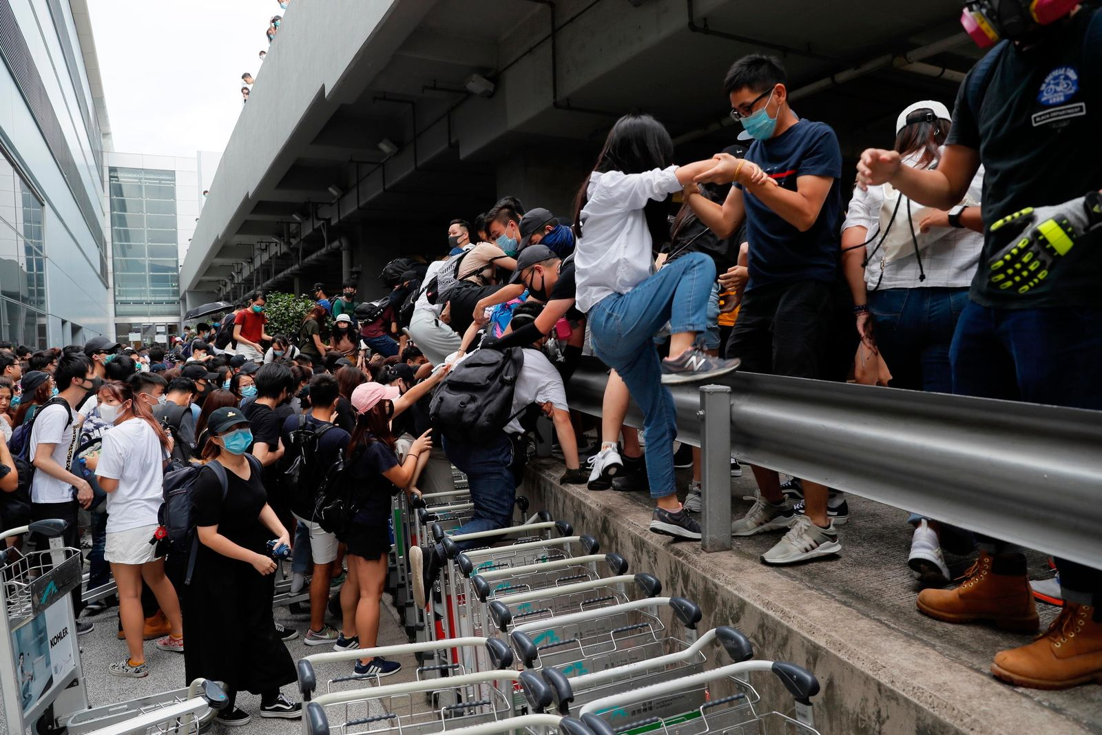 Pro-democracy protestors leave after riot police arrive outside the airport in Hong Kong, Sunday, Sept.1, 2019. (AP Photo/Kin Cheung)