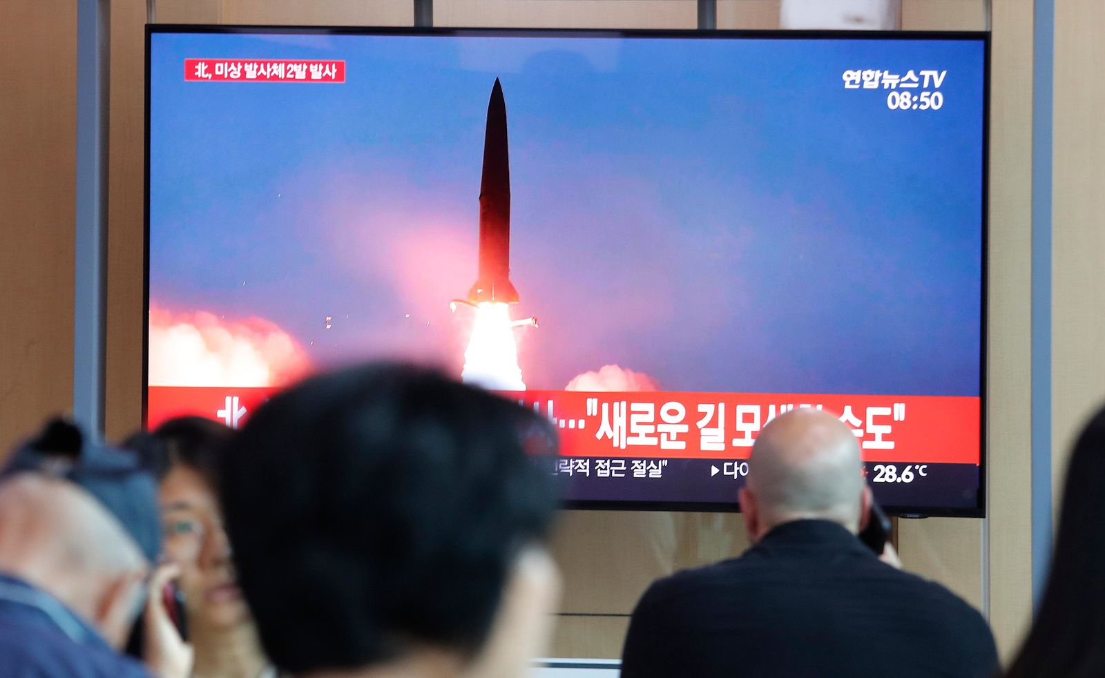 "People watch a TV showing a file image of a North Korea's missile launch during a news program at the Seoul Railway Station in Seoul, South Korea, Tuesday, Aug. 6, 2019. North Korea on Tuesday continued to ramp up its weapons demonstrations by firing unidentified projectiles twice into the sea while lashing out at the United States and South Korea for continuing their joint military exercises that the North says could derail fragile nuclear diplomacy. The sign reads ""North Korea could seek a new road."" (AP Photo/Ahn Young-joon)"