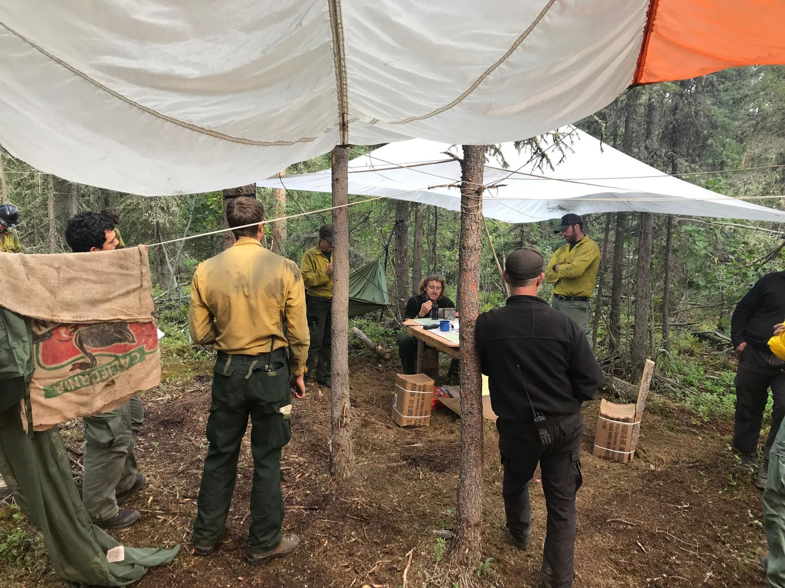 Firefighters standing and talking at their fire camp under white tarps. (Courtesy Medford Crew 10){ }{ }