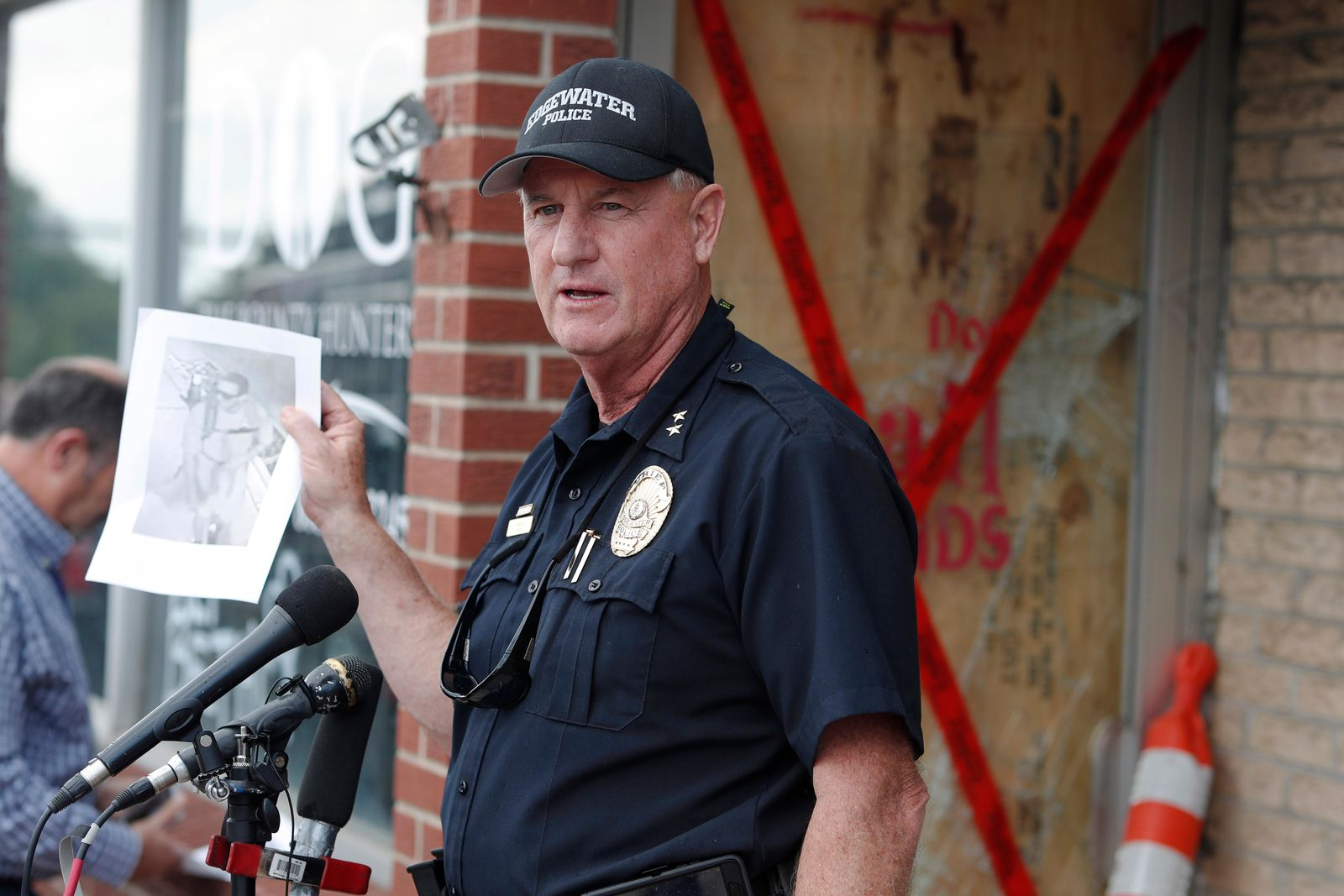 "Edgewater, Colo., Police Chief John Mackey holds up an image of the suspect in the break-in of the storefront owned by Duane ""Dog the Bounty Hunter"" Chapman during a news conference  Friday, Aug. 2, 2019, in Edgewater, Colo. (AP Photo/David Zalubowski)"