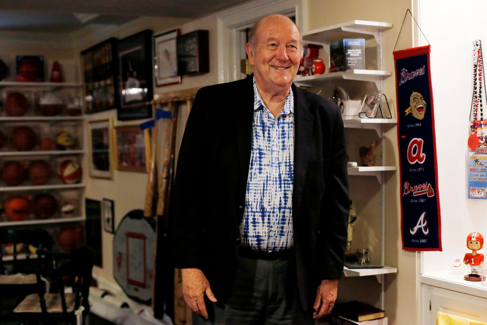 Bob Hope stands in the basement where his collection of sports memorabilia has been displayed for sale, Friday, Aug. 23, 2019, in Stone Mountain, Ga. (AP Photo/Andrea Smith)