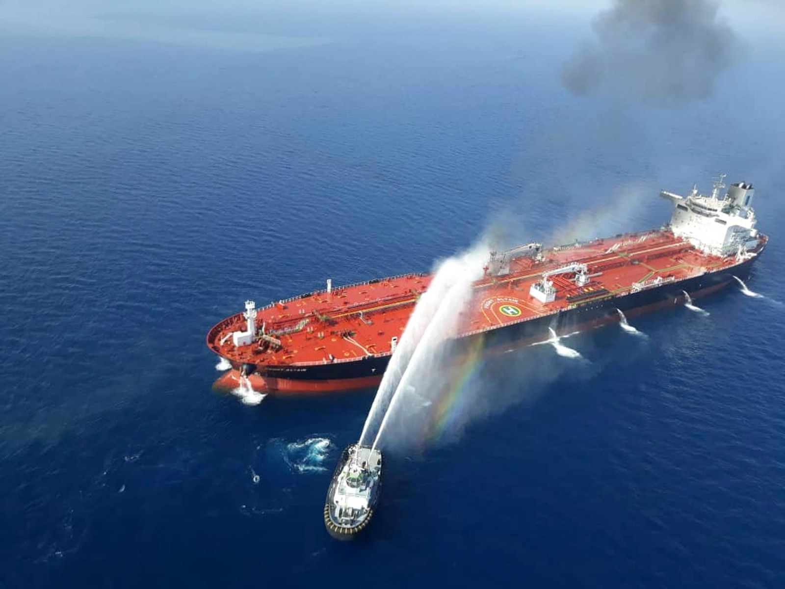 An Iranian navy boat sprays water to extinguish a fire on an oil tanker in the sea of Oman, Thursday, June 13, 2019. Two oil tankers near the strategic Strait of Hormuz came under a suspected attack Thursday, setting one of them ablaze in the latest mysterious assault targeting vessels in a region crucial to global energy supplies amid heightened tension between Iran and the U.S. (AP Photo/Tasnim News Agency)