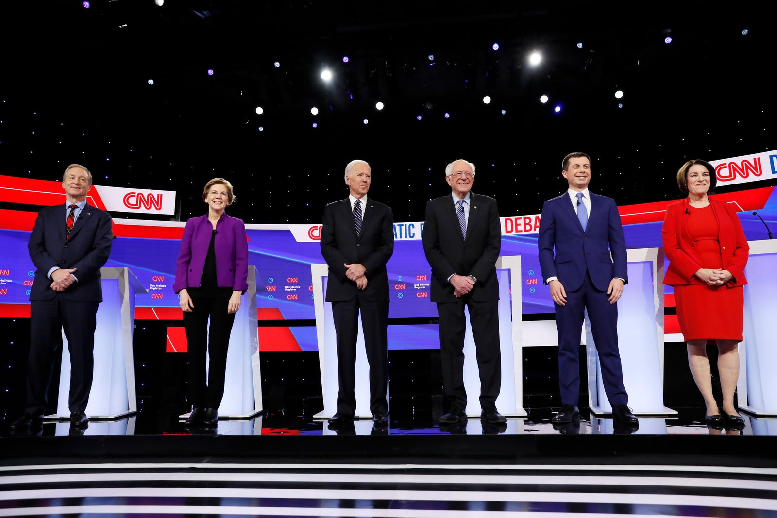 From left, Democratic presidential candidates businessman Tom Steyer, Sen. Elizabeth Warren, D-Mass., former Vice President Joe Biden, Sen. Bernie Sanders, I-Vt., former South Bend Mayor Pete Buttigieg, and Sen. Amy Klobuchar, D-Minn., stand on stage, Tuesday, Jan. 14, 2020, before a Democratic presidential primary debate hosted by CNN and the Des Moines Register in Des Moines, Iowa. (AP Photo/Charlie Neibergall)