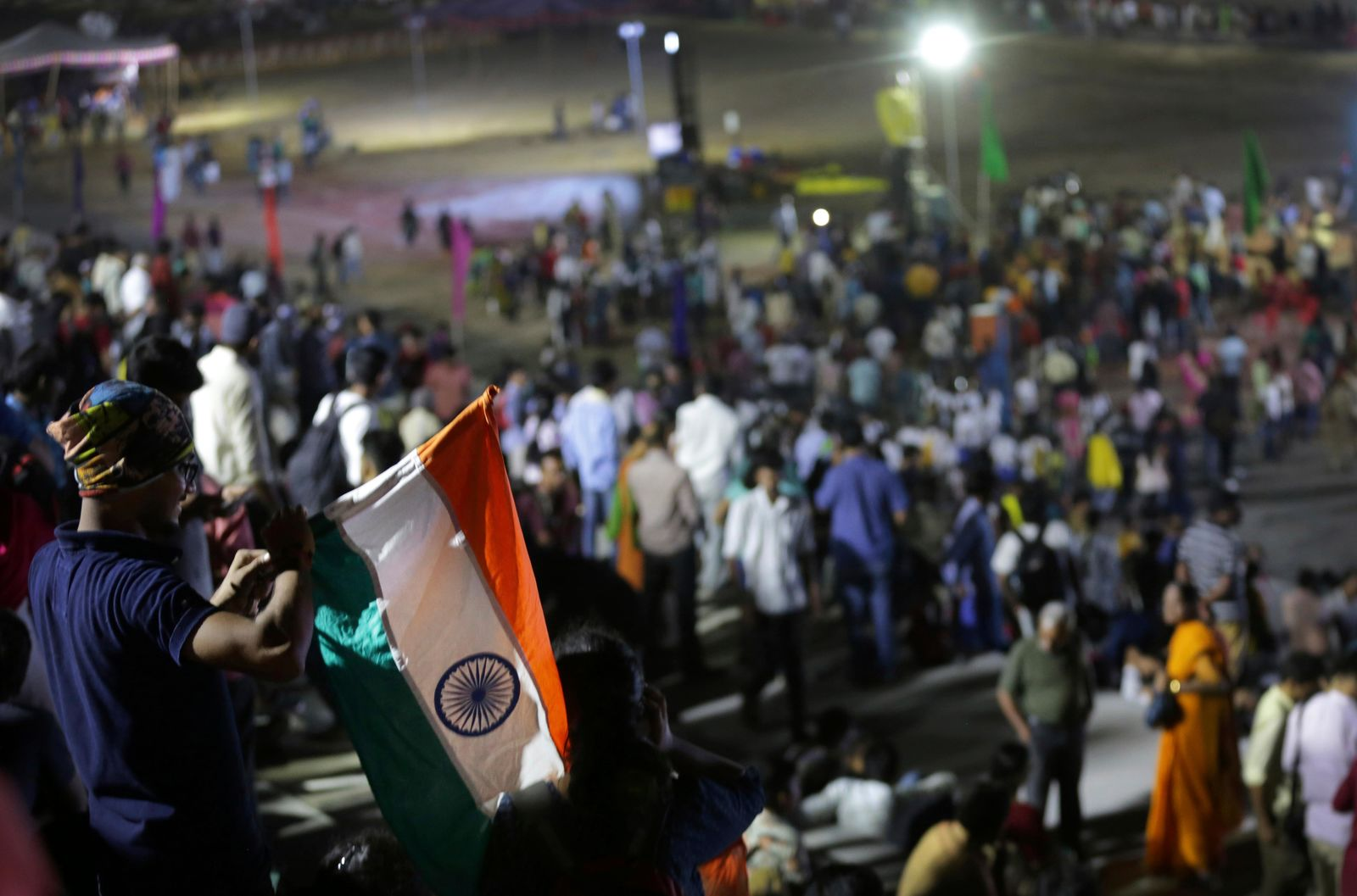 An Indian spectator folds Indian national flag as others leave after the Chandrayaan-2 mission was aborted at Sriharikota, in southern India, Monday, July 15, 2019. (AP Photo/Manish Swarup)