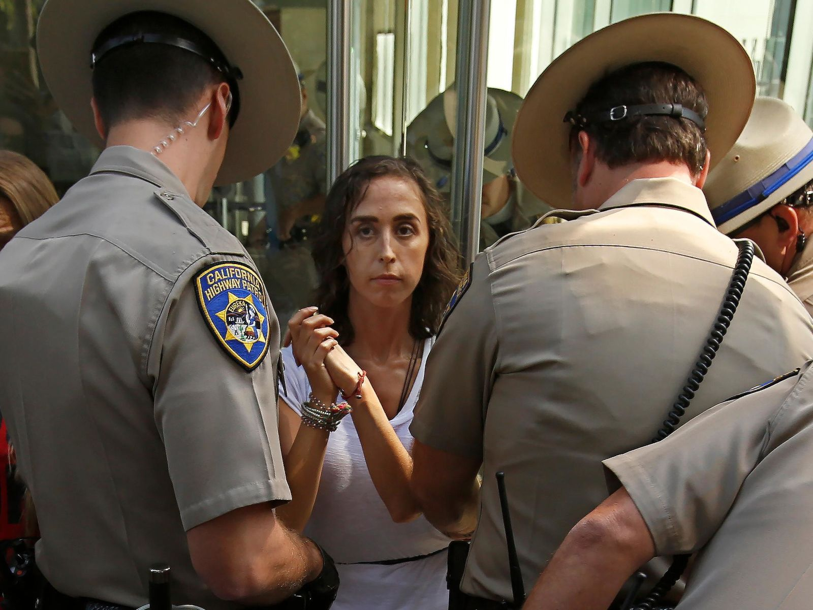 California Highway Patrol officers take into custody an opponent of recently passed legislation to tighten the rules on giving exemptions for vaccinations, after she cabled herself to the doors of the state Capitol in Sacramento, Calif., Monday, Sept. 9, 2019. The state Assembly approved the companion bill, Monday, with changes demanded by Gov Gavin Newsom as a condition of signing the controversial vaccine bill SB276 which was passed by the Legislature last week.(AP Photo/Rich Pedroncelli)