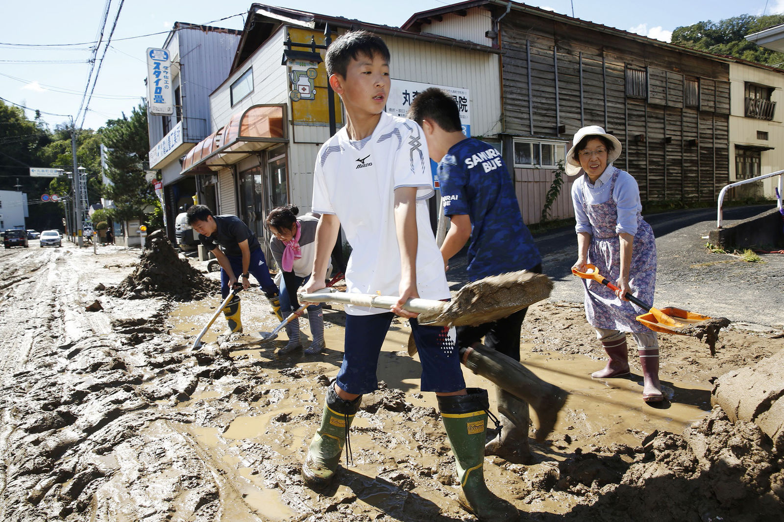 Students and residents scoop dirt as the town is flooded Typhoon Hagibis, in Marumori, Miyagi prefecture, northern Japan, Sunday, Oct. 13, 2019. (Kyodo News via AP)