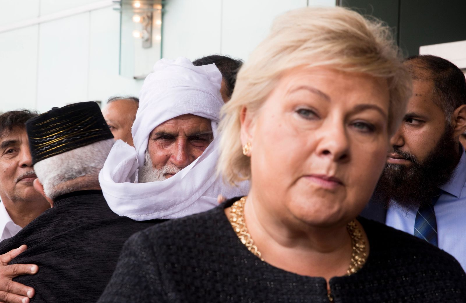 Norway's Prime Minister Erna Solberg and Mohamed Rafiq background centre left, stand outside Thon Hotel in Baerum, Norway, Sunday, Aug. 11, 2019. (Terje Pedersen  /NTB scanpix via AP)