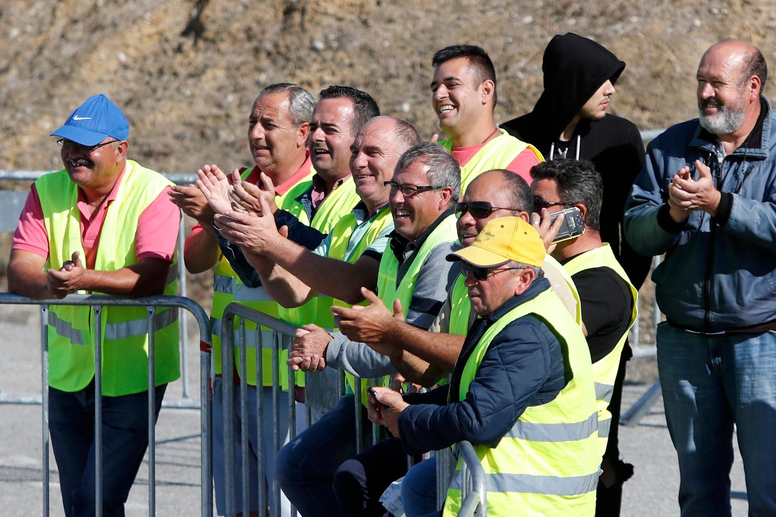 Tanker truck drivers on strike applaud a fellow driver leaving a fuel depot in Aveiras, outside Lisbon, Monday, Aug. 12, 2019. (AP Photo/Armando Franca)