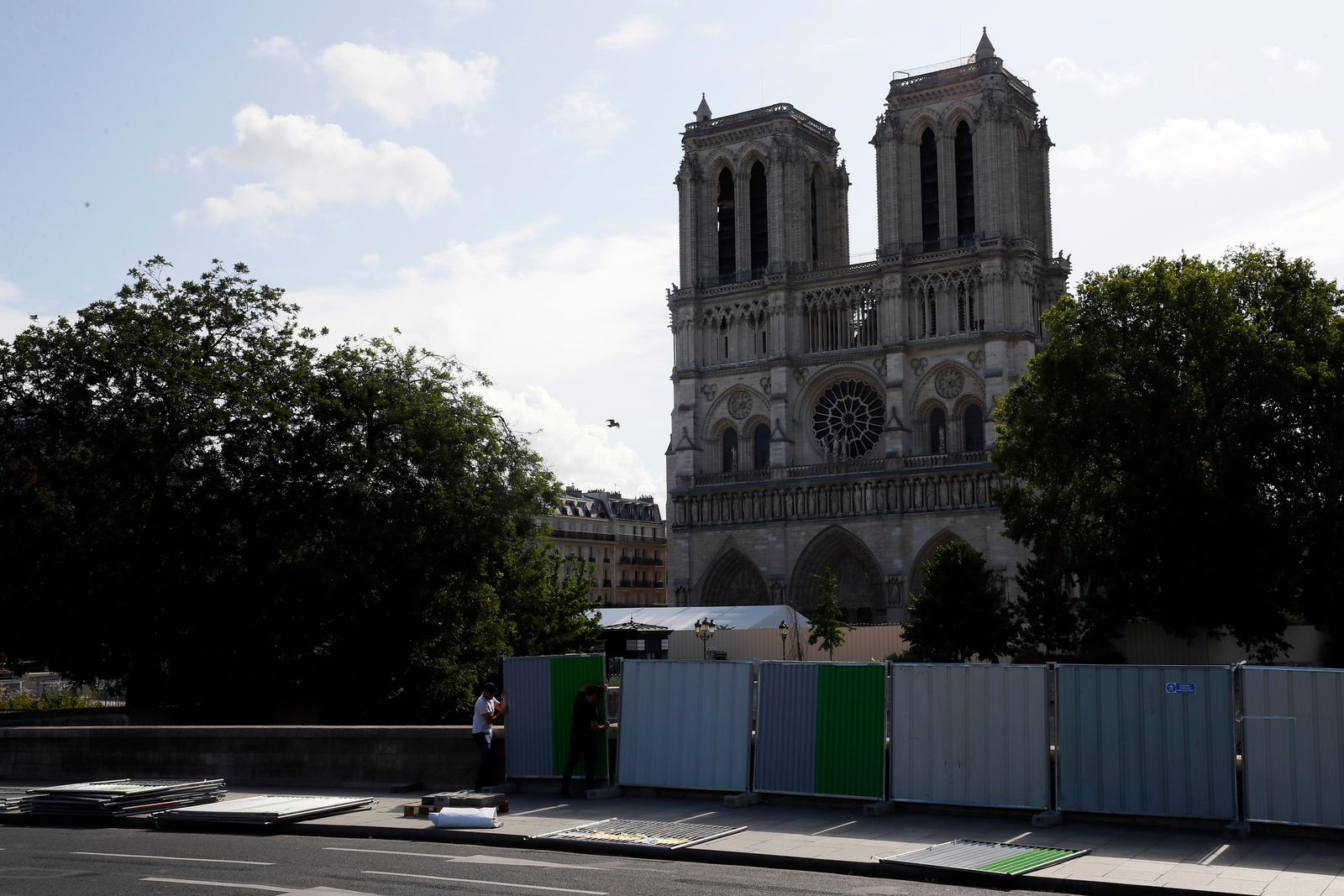 Workers install high fences on a bridge around Notre Dame cathedral in Paris, Tuesday, Aug. 13, 2019.(AP Photo/Francois Mori)