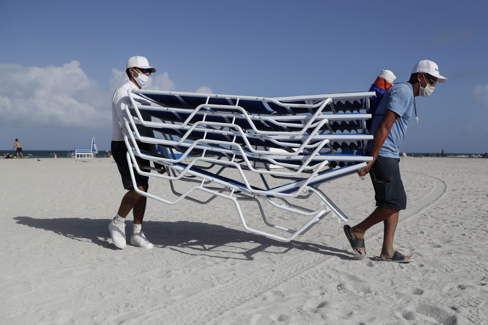 Workers remove chairs from the beach in preparation for Hurricane Isaias, Friday, July 31, 2020, in Miami Beach, Fla. Forecasters declared a hurricane warning for parts of the Florida coast Friday as Hurricane Isaias drenched the Bahamas on track for the U.S. East Coast. (AP Photo/Lynne Sladky)