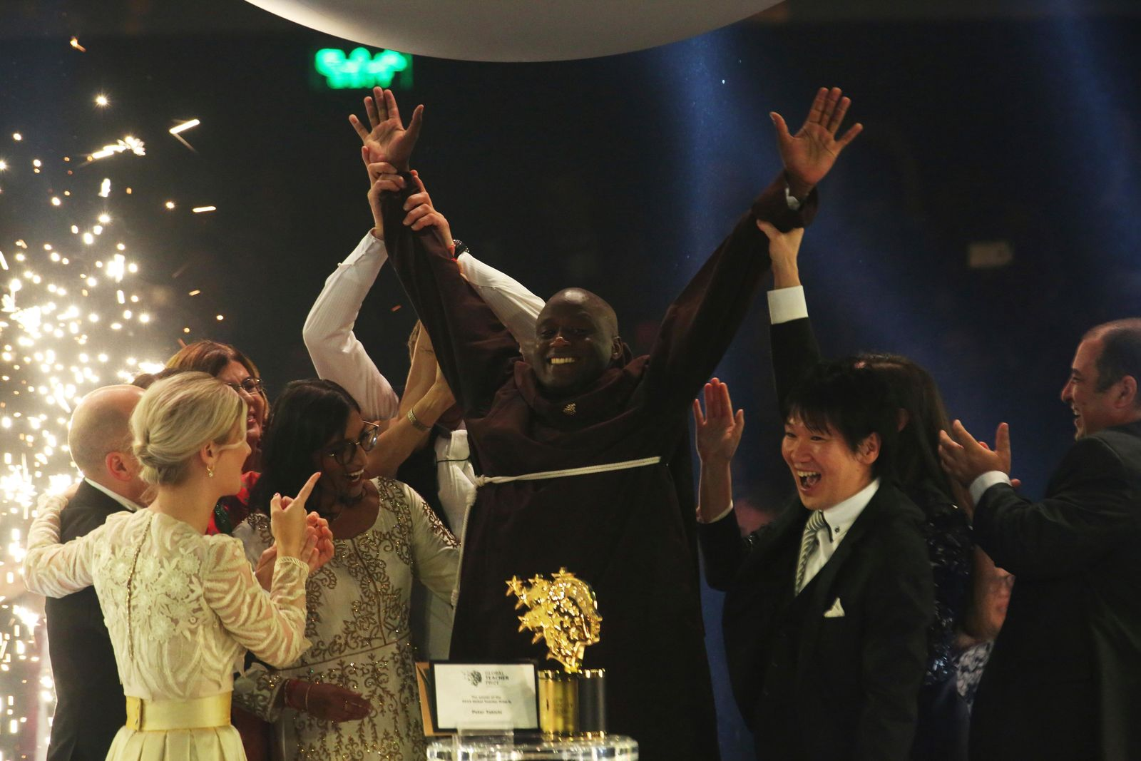 Kenyan teacher Peter Tabichi, center, reacts after winning the $1 million Global Teacher Prize in Dubai, United Arab Emirates, Sunday, March 24, 2019.{ } (AP Photo/Jon Gambrell)