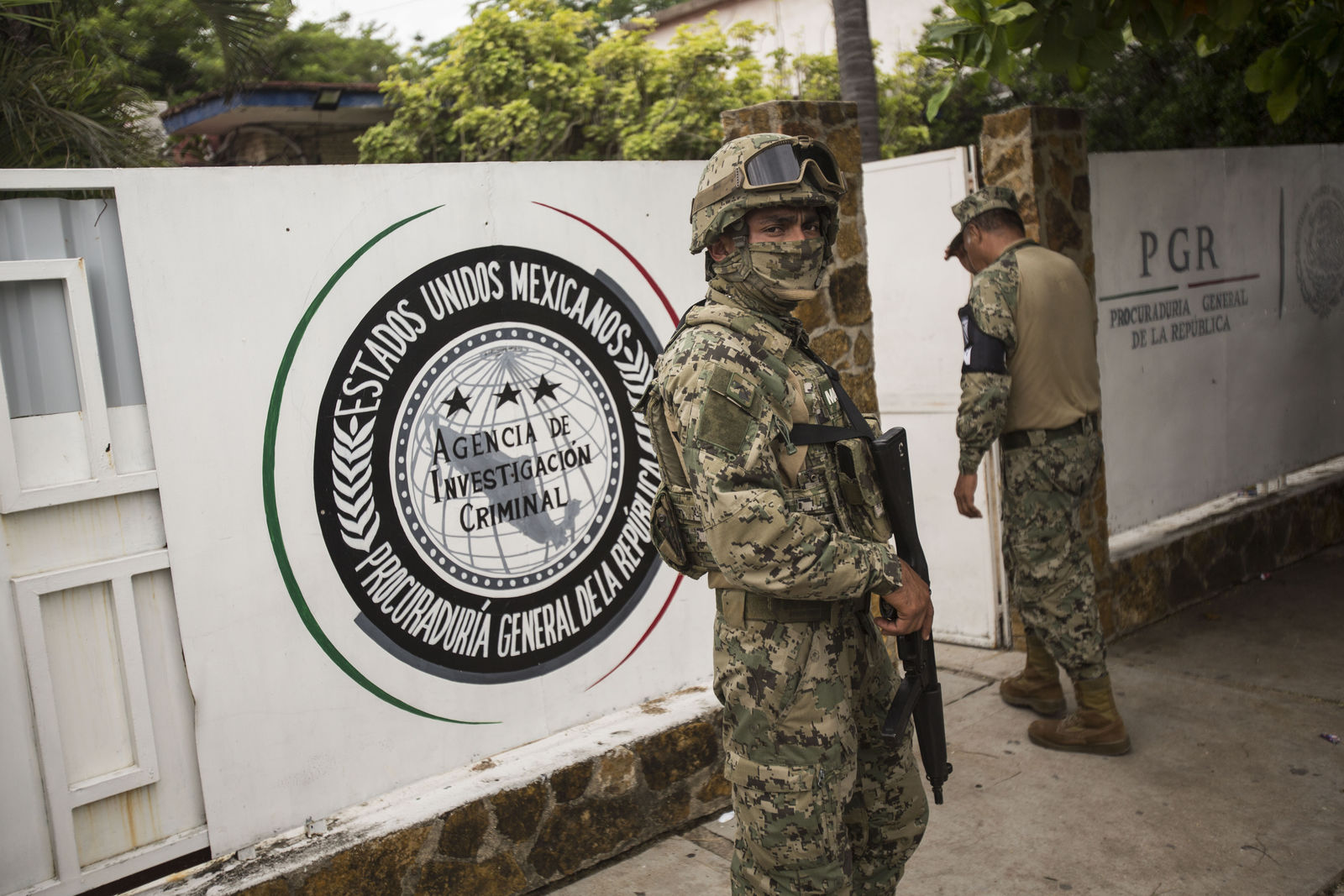 A marine, front, and National Guard, behind, stand guard outside an office of the General Attorney where migrants are brought before being transferred to Tapachula from Arriaga, Mexico, Sunday, June 23, 2019. Mexico has completed its deployment of 6,000 National Guard agents to help control the flow of migrants headed toward the U.S. and filled immigration agency posts to regulate border crossings, the government said Friday. (AP Photo/Oliver de Ros)