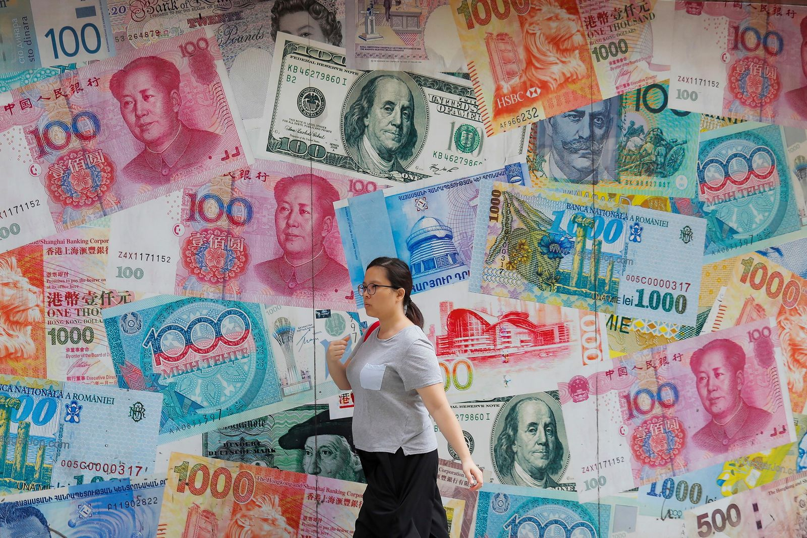 FILE _ In this Aug. 6, 2019, file photo, a woman walks by a money exchange shop decorated with different countries currency banknotes at Central, a business district in Hong Kong. China has announced it will raise tariffs on $75 billion of U.S. products in retaliation for President Donald Trump's planned Sept. 1 duty increase in a war over trade and technology policy. (AP Photo/Kin Cheung, File)