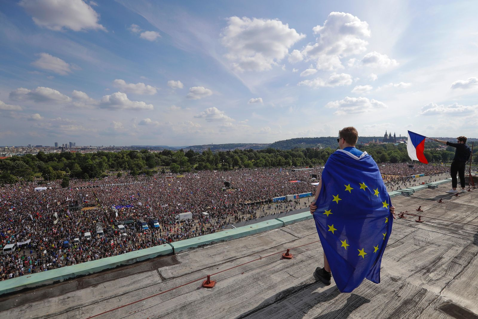 A man wrapped in in an European Union flag watches protesters gather in Prague, Czech Republic, Sunday, June 23, 2019. Protesters are on calling on Czech Prime Minister Andrej Babis to step down over fraud allegations and subsidies paid to his former companies. (AP Photo/Petr David Josek)