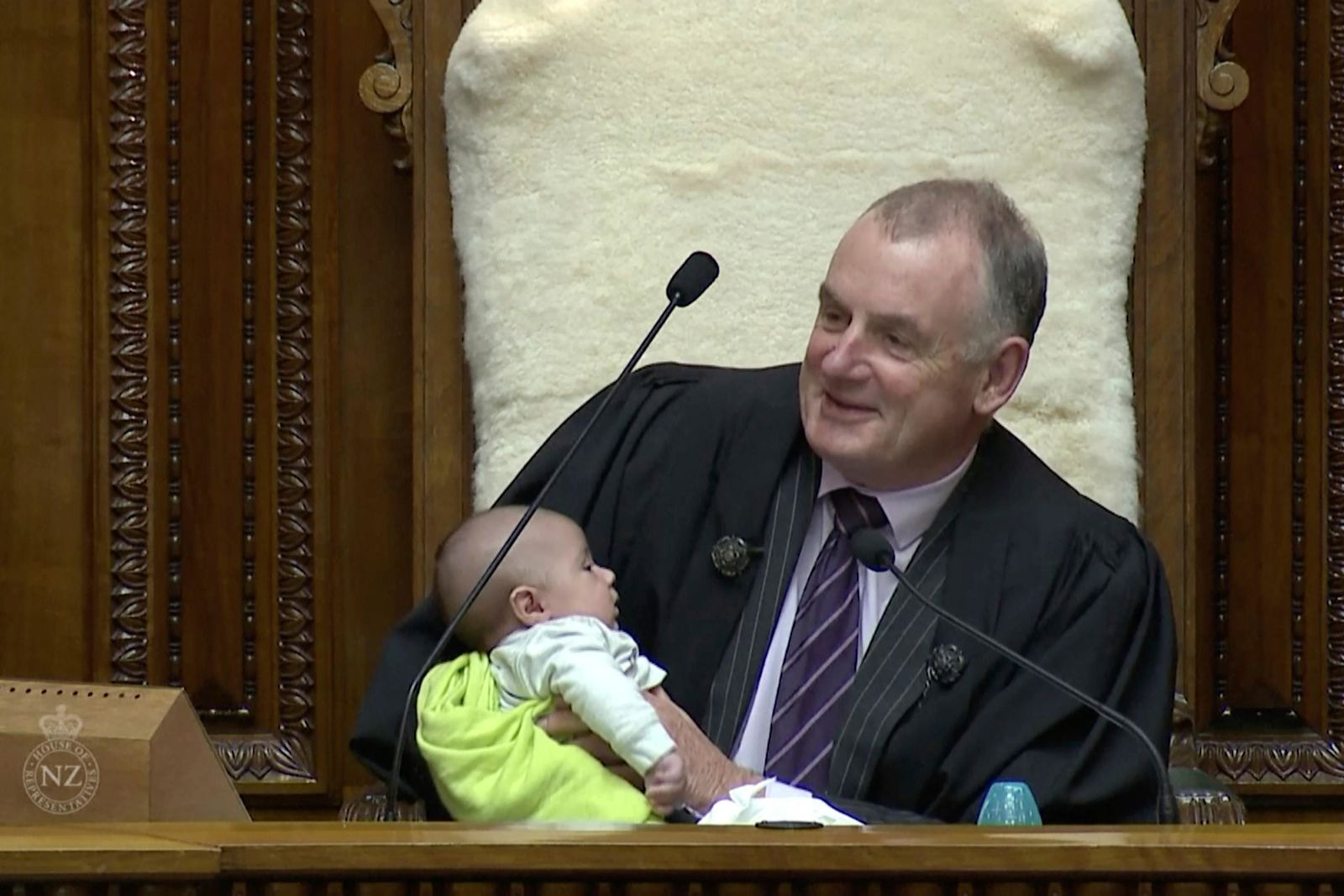 In this Wednesday, Aug. 21, 2019, image from video, New Zealand House Speaker Trevor Mallard cradles lawmaker Tamati Coffey's baby, Tutanekai Smith-Coffey, in his arms while presiding over a debate in parliament in Wellington, New Zealand. (Parliament TV via AP)
