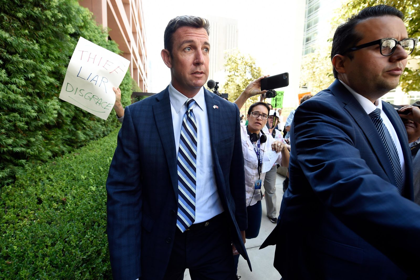 U.S. Rep. Duncan Hunter, center, leaves an arraignment hearing Thursday, Aug. 23, 2018, in San Diego. Hunter and his wife Margaret pleaded not guilty Thursday to charges they illegally used his campaign account for personal expenses. (AP Photo/Denis Poroy)
