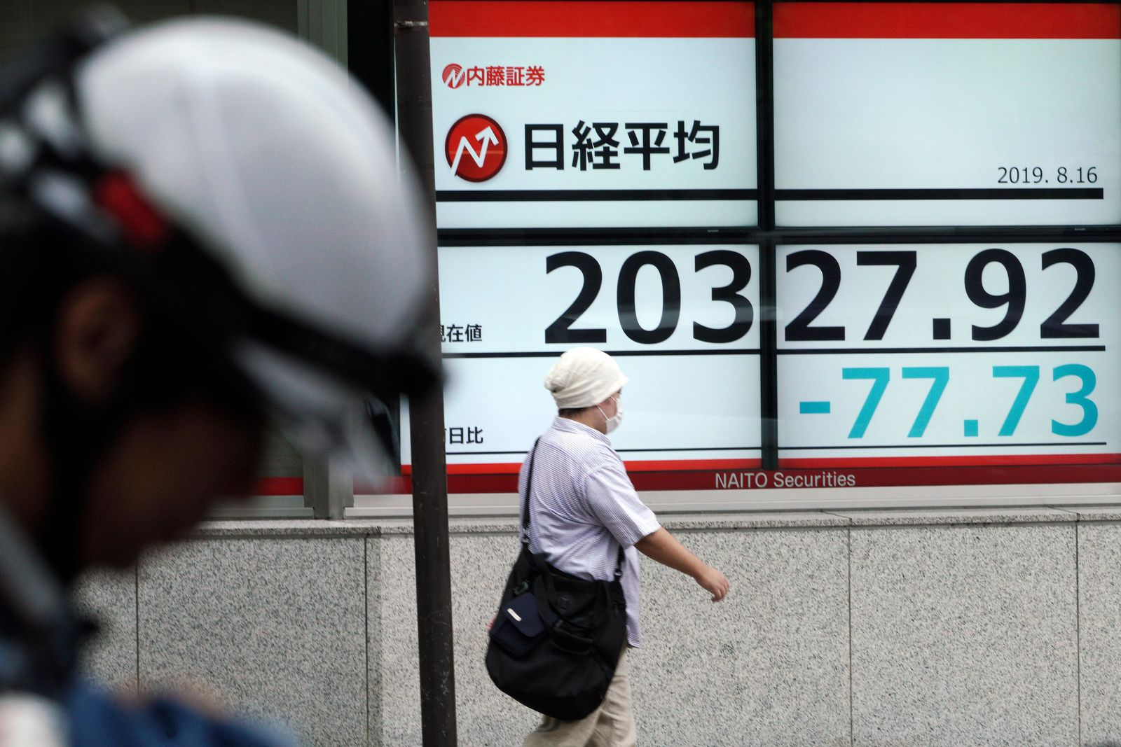 A man walks past an electronic stock board showing Japan's Nikkei 225 index at a securities firm in Tokyo Friday, Aug. 16, 2019. Asian shares were mixed Friday as turbulence continued on global markets amid ongoing worries about U.S.-China trade conflict. (AP Photo/Eugene Hoshiko)