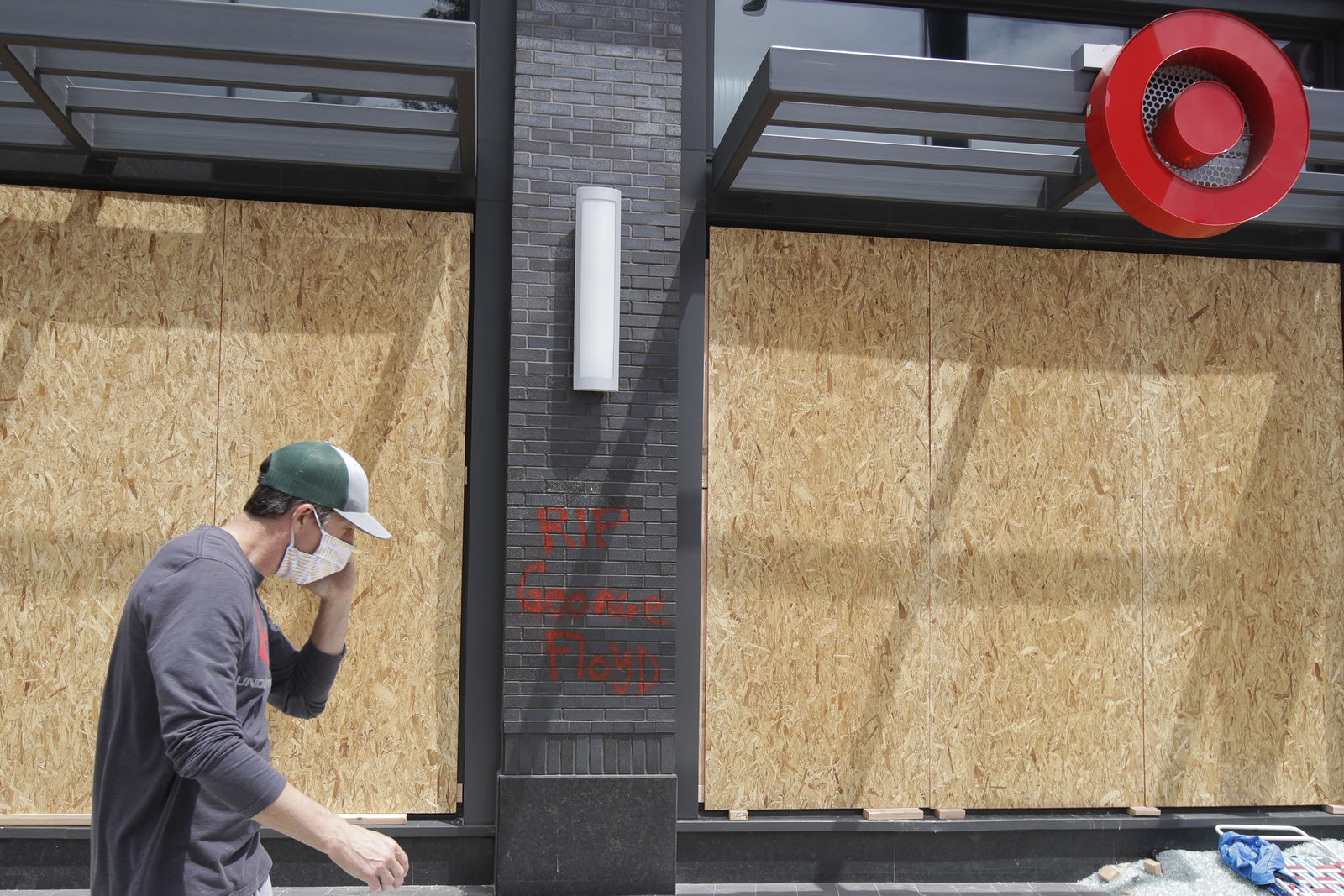 A worker walks past boarded up windows at a Target store in Oakland, Calif., Saturday, May 30, 2020, that was damaged during protests over the death of George Floyd. (AP Photo/Jeff Chiu)