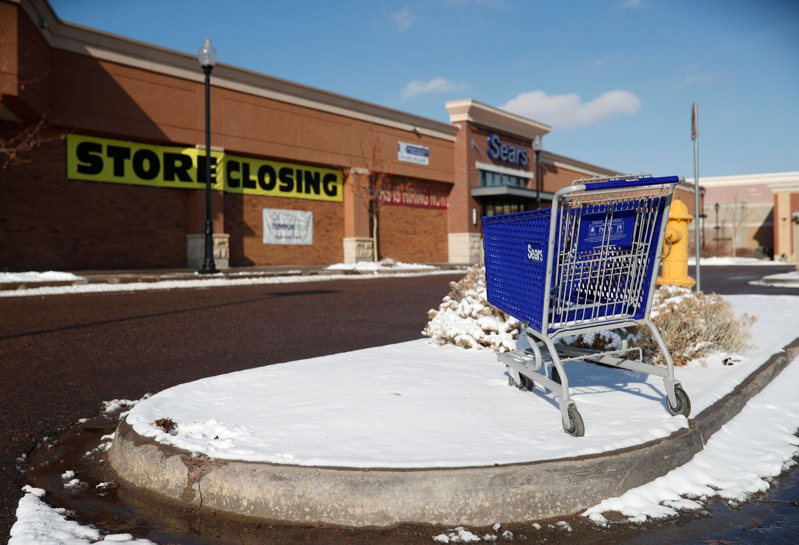 FILE- In this Tuesday, Jan. 1, 2019, file photo, an empty shopping cart sits in the snow outside a Sears store in the Streets of Southglenn mall in Littleton, Colo. (AP Photo/David Zalubowski, File)