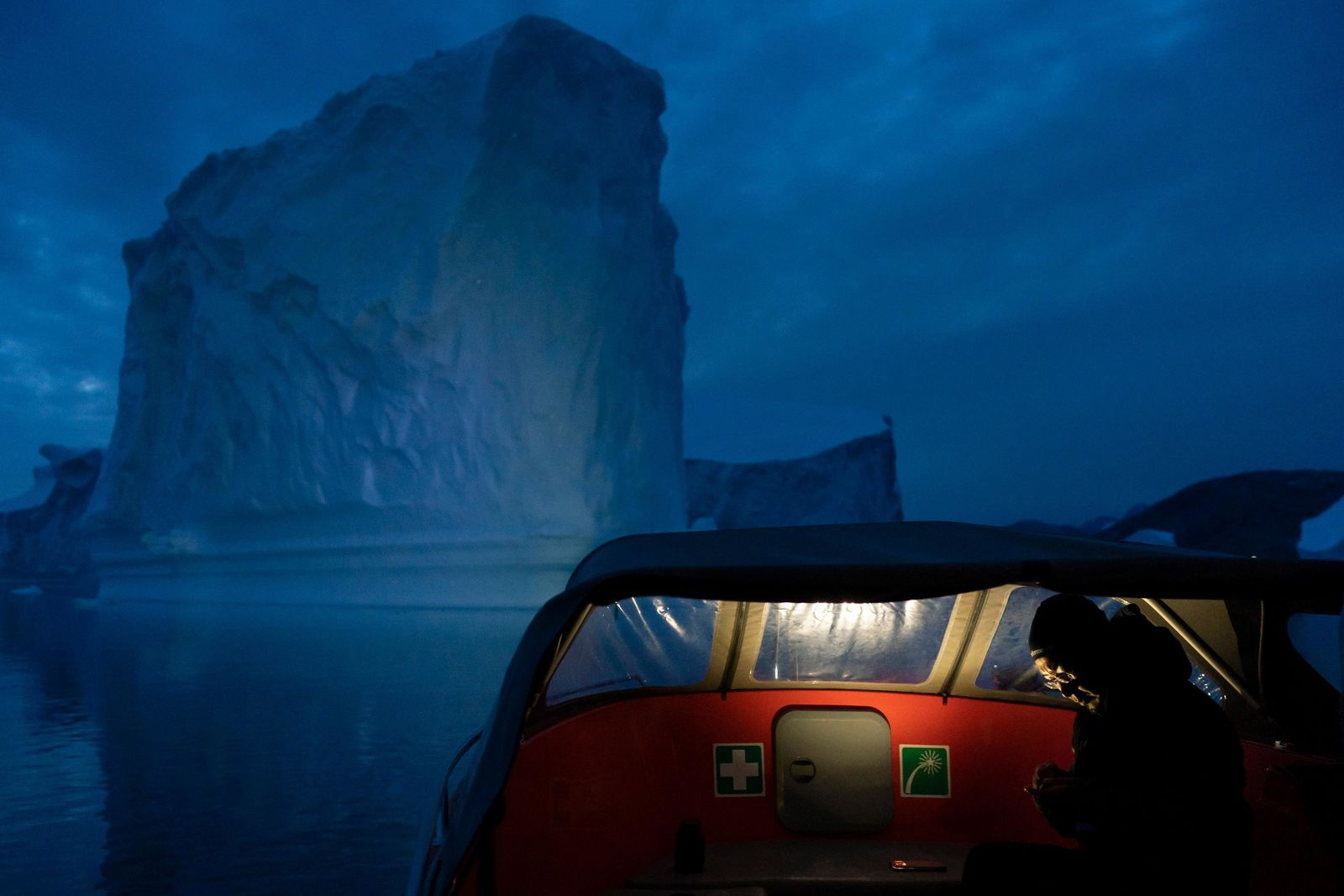 In this Aug. 15, 2019, photo, a boat navigates at night next to a large iceberg in eastern Greenland. (AP Photo/Felipe Dana)