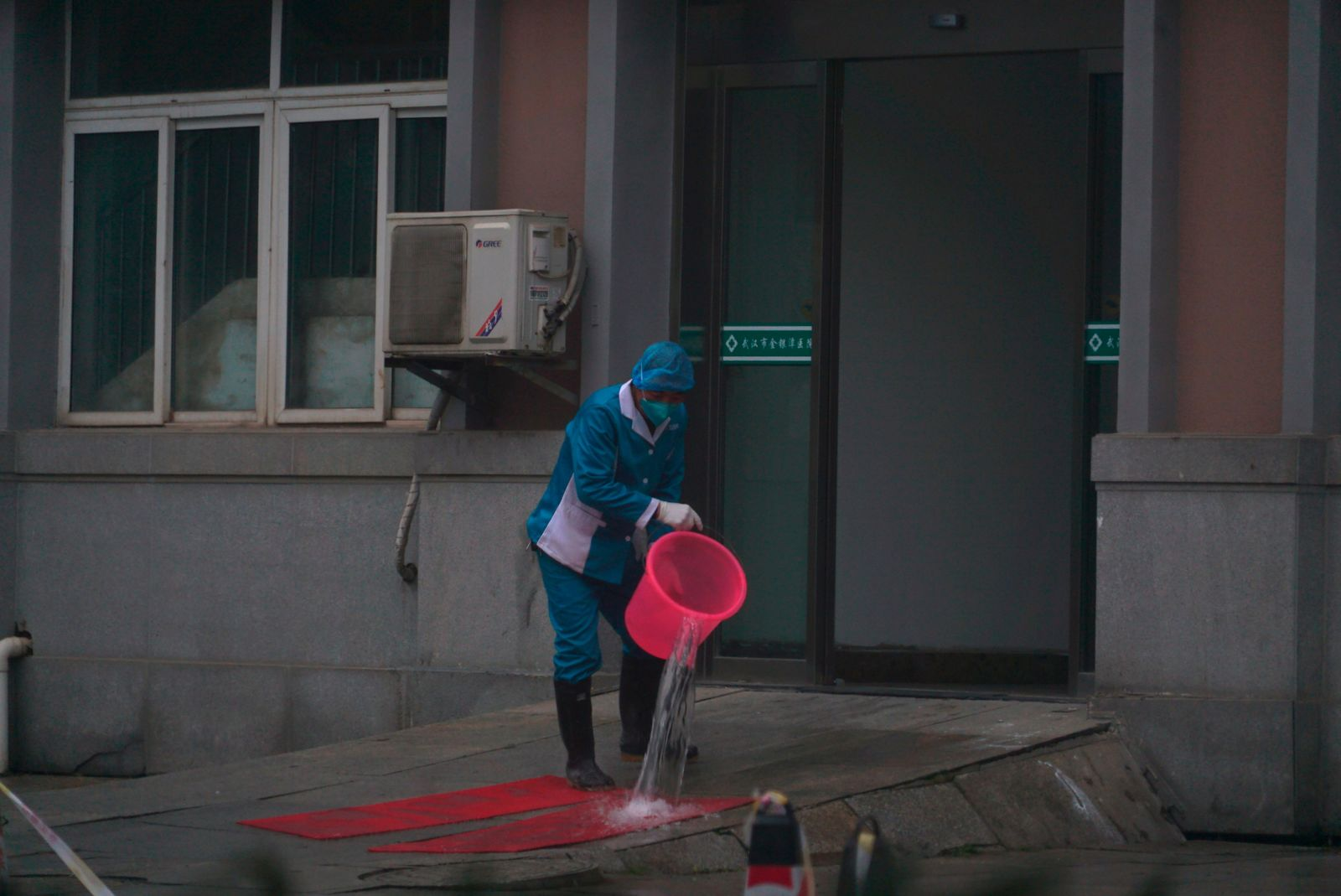 Hospital staff wash the emergency entrance of Wuhan Medical Treatment Center, where some infected with a new virus are being treated, in Wuhan, China, Wednesday, Jan. 22, 2020. The number of cases of a new coronavirus from Wuhan has risen to over 400 in China health authorities said Wednesday. (AP Photo/Dake Kang)