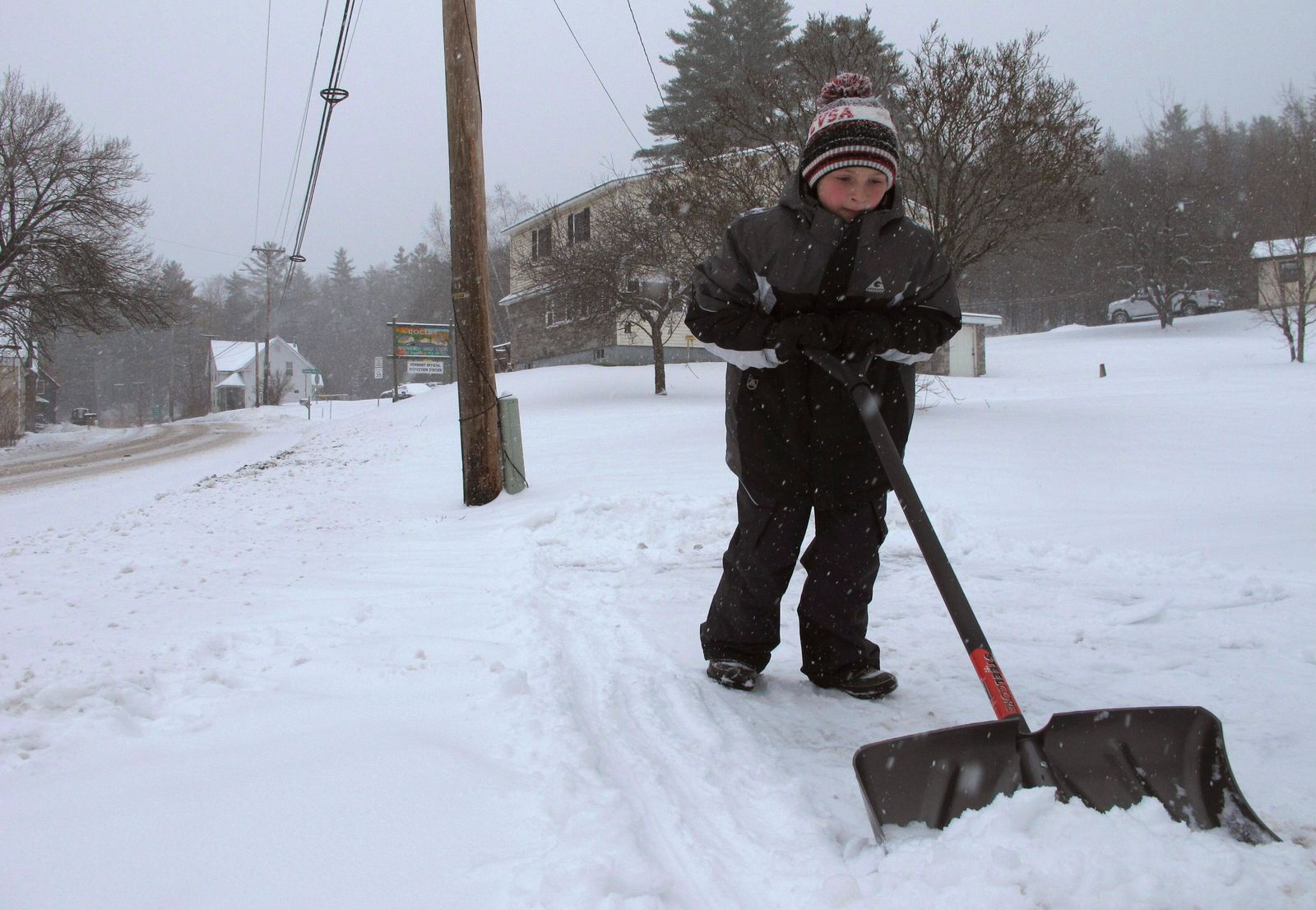 Kaiden Rogers shovels snow from his driveway on Tuesday, Nov. 12, 2019 in Marshfield, Vt.  A wintry mix has swept into northern New England, with hundreds of schools closed or delayed in Vermont due to snow, and slick conditions in New Hampshire and Maine.  (AP Photo/Lisa Rathke)