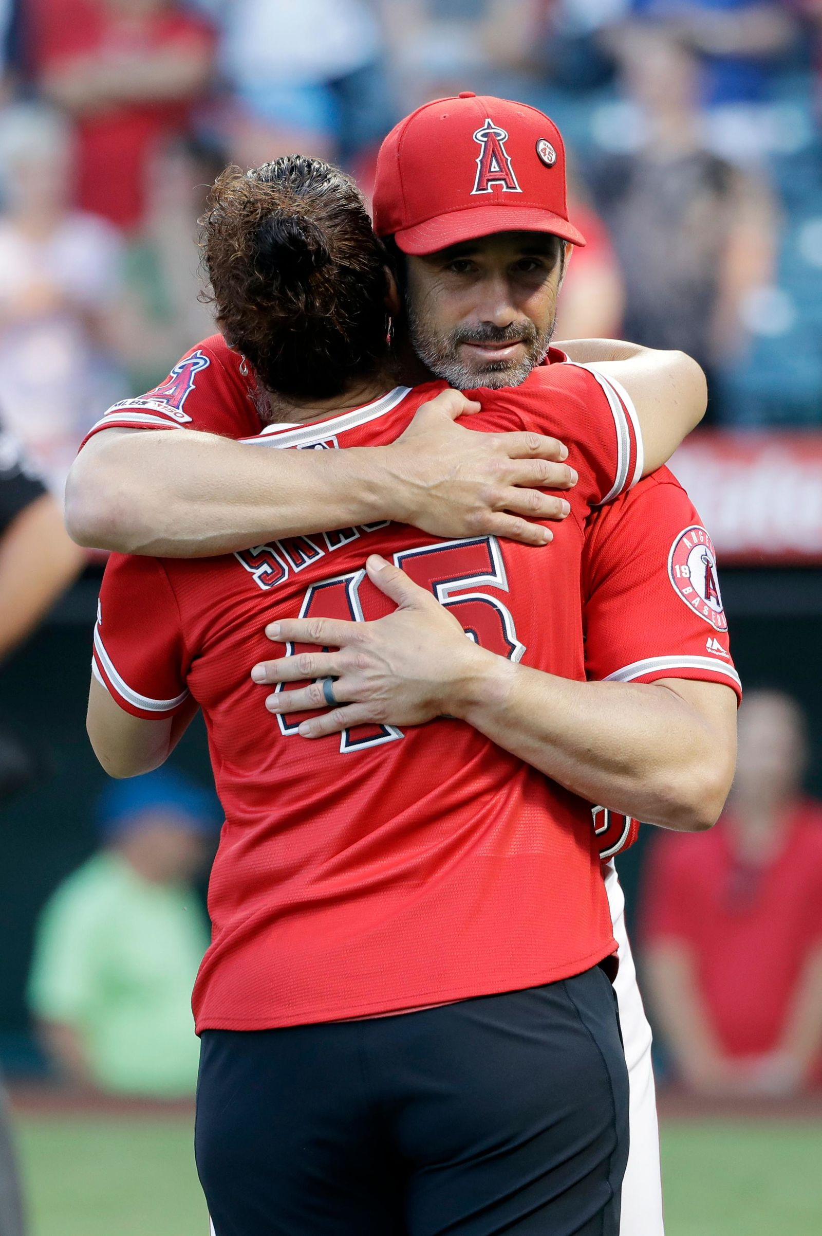 Los Angeles Angels manager Brad Ausmus, facing camera, hugs the late pitcher Tyler Skaggs' mother, Debbie Hetman, before the team's baseball game against the Seattle Mariners on Friday, July 12, 2019, in Anaheim, Calif. (AP Photo/Marcio Jose Sanchez)