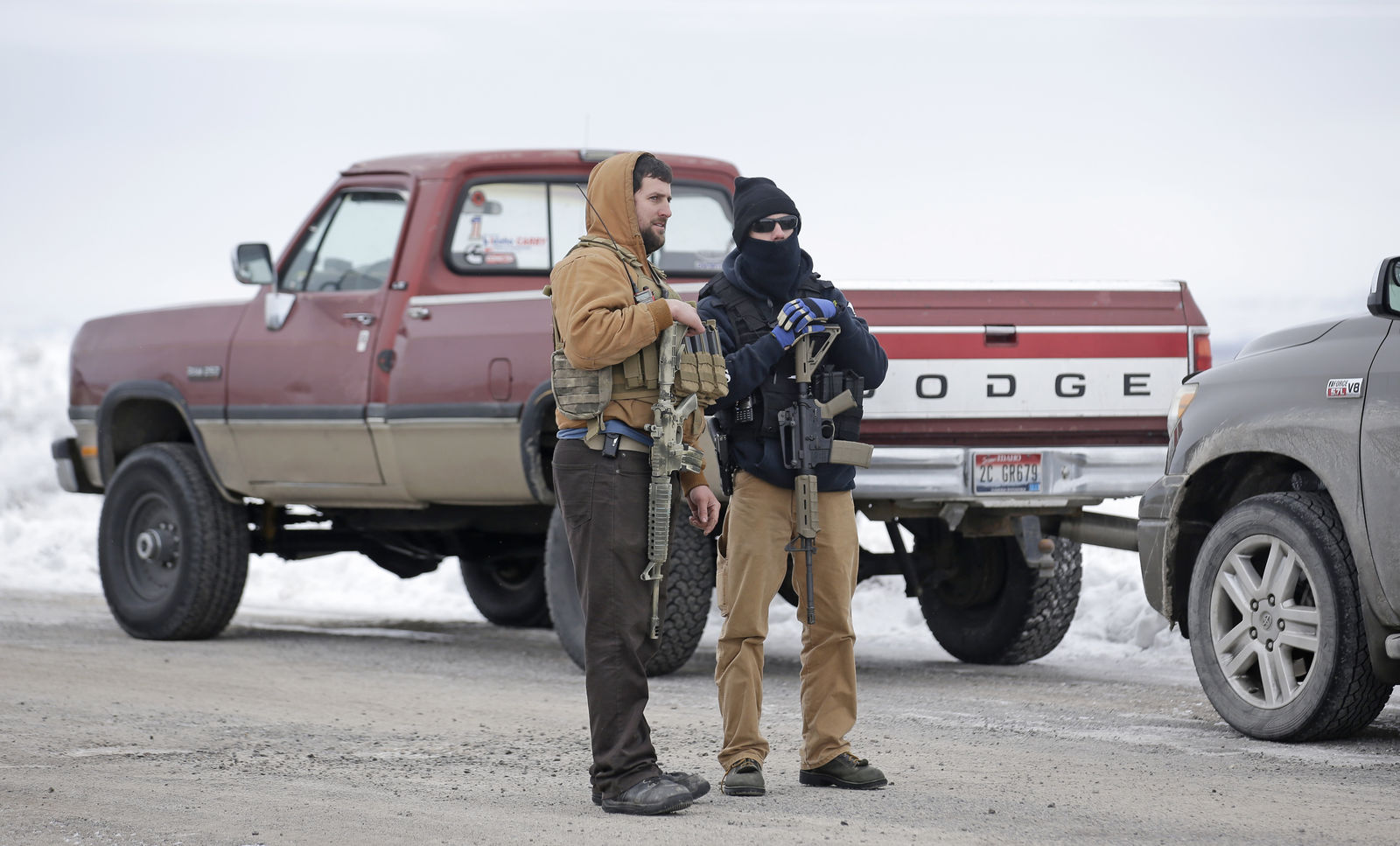 "Men stand guard after members of the ""3% of Idaho"" group along with several other organizations arrived at the Malheur National Wildlife Refuge Saturday, Jan. 9, 2016, near Burns, Ore. A small, armed group has been occupying a remote national wildlife refuge in Oregon for a week to protest federal land use policies. (AP Photo/Rick Bowmer)"