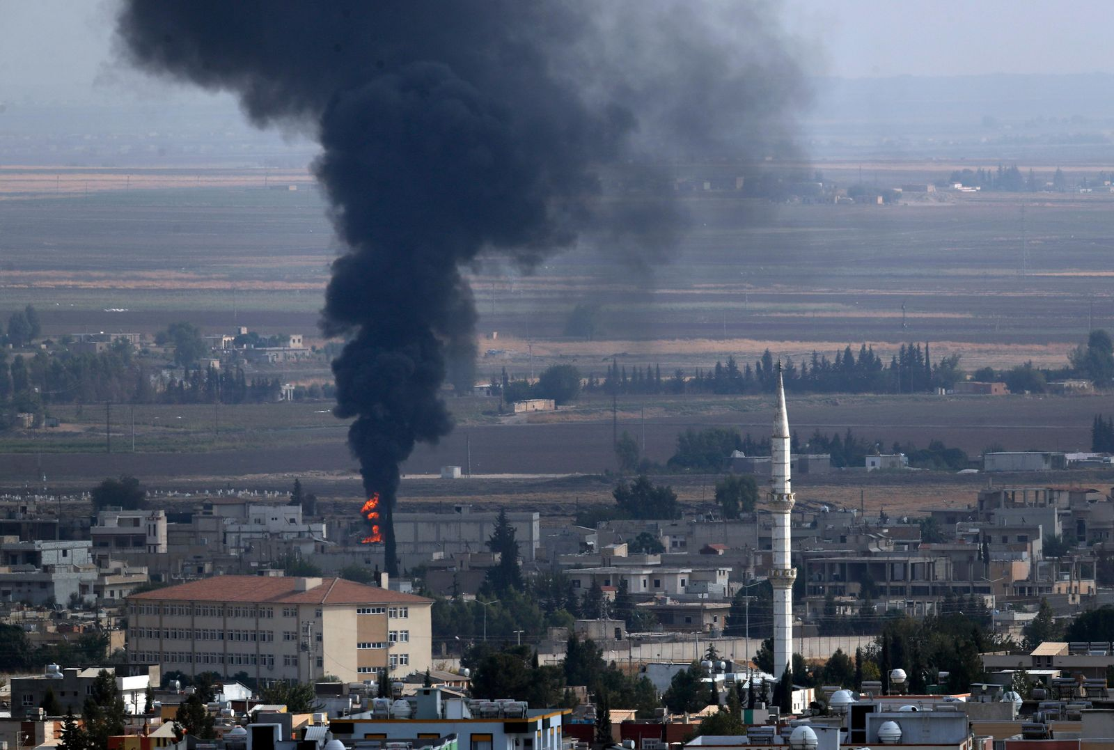 In this photo taken from the Turkish side of the border between Turkey and Syria, in Ceylanpinar, Sanliurfa province, southeastern Turkey, smoke billows from a fire in Ras al-Ayn, Syria, Friday, Oct. 18, 2019. (AP Photo/Lefteris Pitarakis)