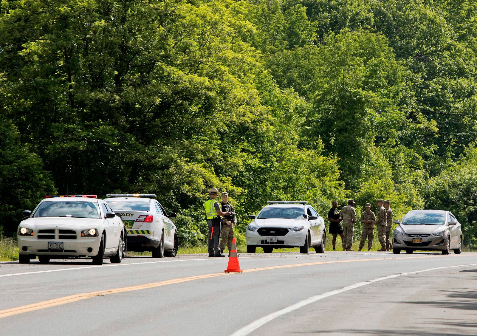 Military police and civilian first responders stand along Route 293 in response to a rollover of an armored personnel vehicle in which at least one person was killed on Thursday, June 6, 2019, in Cornwall, N.Y.(AP Photo/Allyse Pulliam)