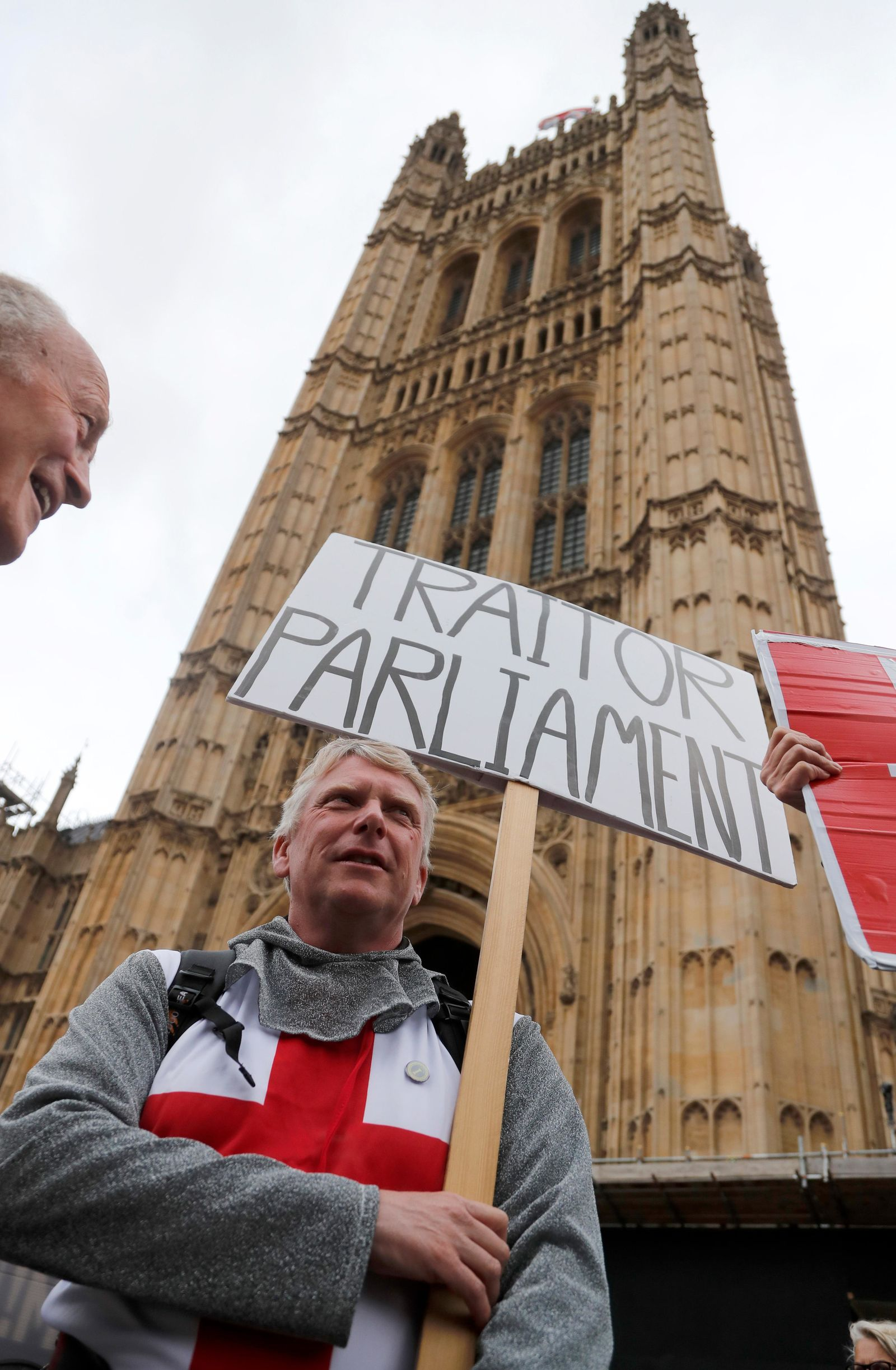 A protestor shows a poster opposite parliament in London, Monday, Sept. 9, 2019. (AP Photo/Frank Augstein)
