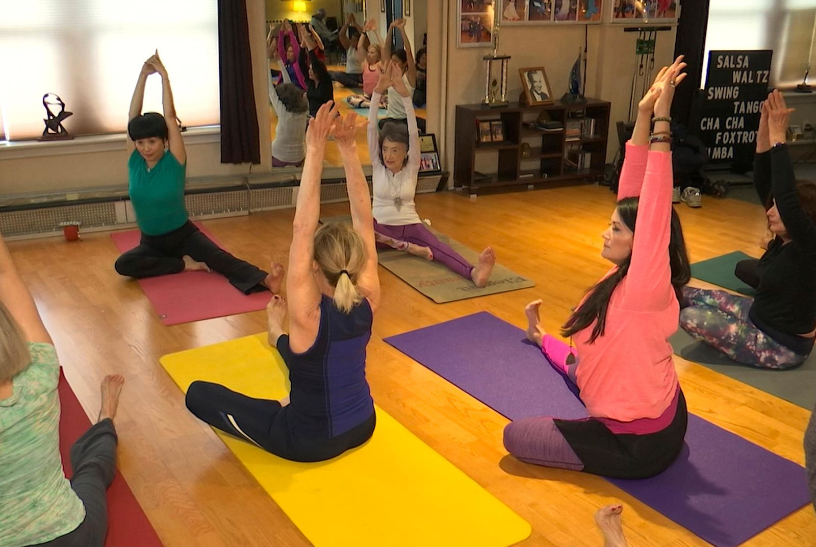 In this April 5, 2019, image made from a video, 100-year-old Tao Porchon-Lynch, rear right,  teaches a yoga class in Hartsdale, N.Y. (AP Photo/Ted Shaffrey)