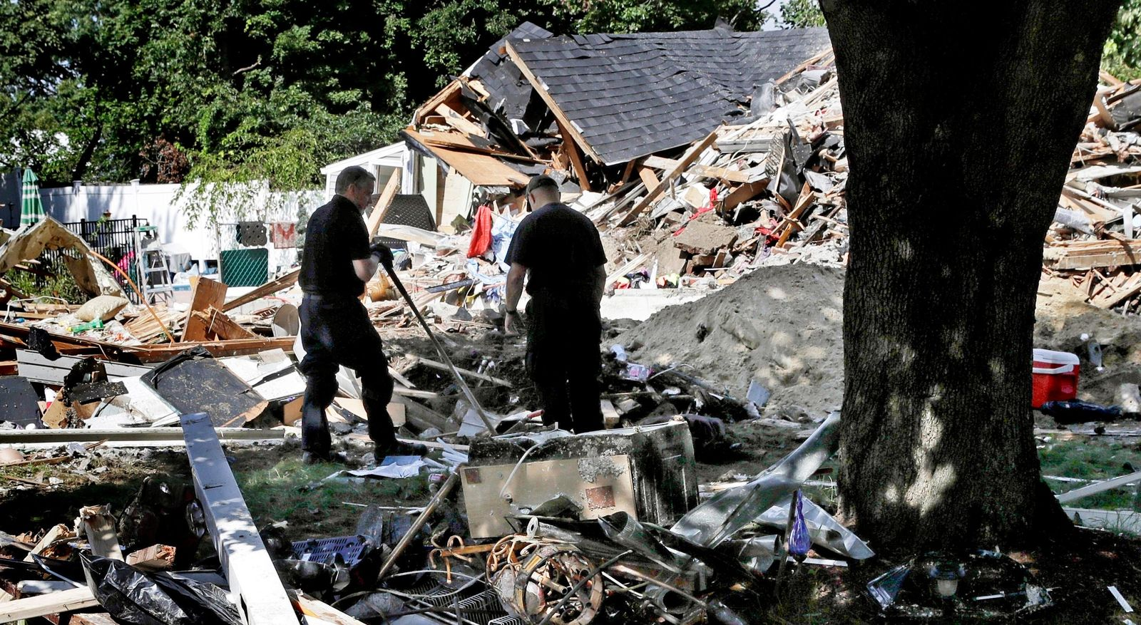 FILE - In this Sep. 21, 2018, file photo, fire investigators pause while searching the debris at a home which exploded following a gas line failure in Lawrence, Mass. (AP Photo/Charles Krupa, File)