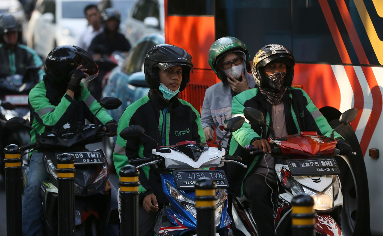 Grab driver sitting on their motorcycles wait for passengers in Jakarta, Indonesia, Monday, July 29, 2019. Japanese technology company Softbank and Southeast Asian ride hailing app Grab said Monday, July 29, 2019, they're investing $2 billion in Indonesia over the next five years. (AP Photo/Achmad Ibrahim)
