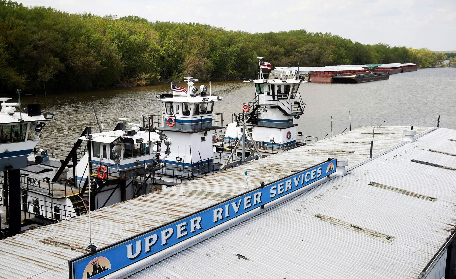 In this Tuesday, May 14, 2019 photo, empty barges, background right, are moored at the Upper River Services along with tug boats on the Mississippi River in St. Paul, Minn., as spring flooding interrupts shipments on the river.{ } (AP Photo/Jim Mone)