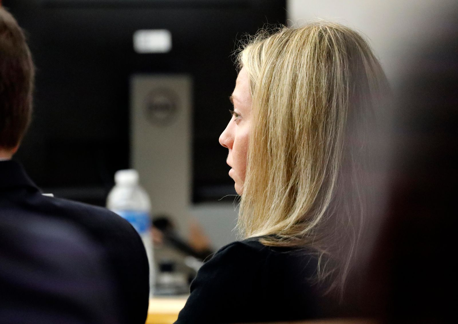 Fired Dallas police officer Amber Guyger listens as friends, family and coworkers speak in her defense during the sentencing phase of her murder trial, Wednesday, Oct. 2, 2019, in Dallas.  Guyger, who said she fatally shot her unarmed, black neighbor Botham Jean after mistaking his apartment for her own, was found guilty of murder the day before. (Tom Fox/The Dallas Morning News via AP, Pool)