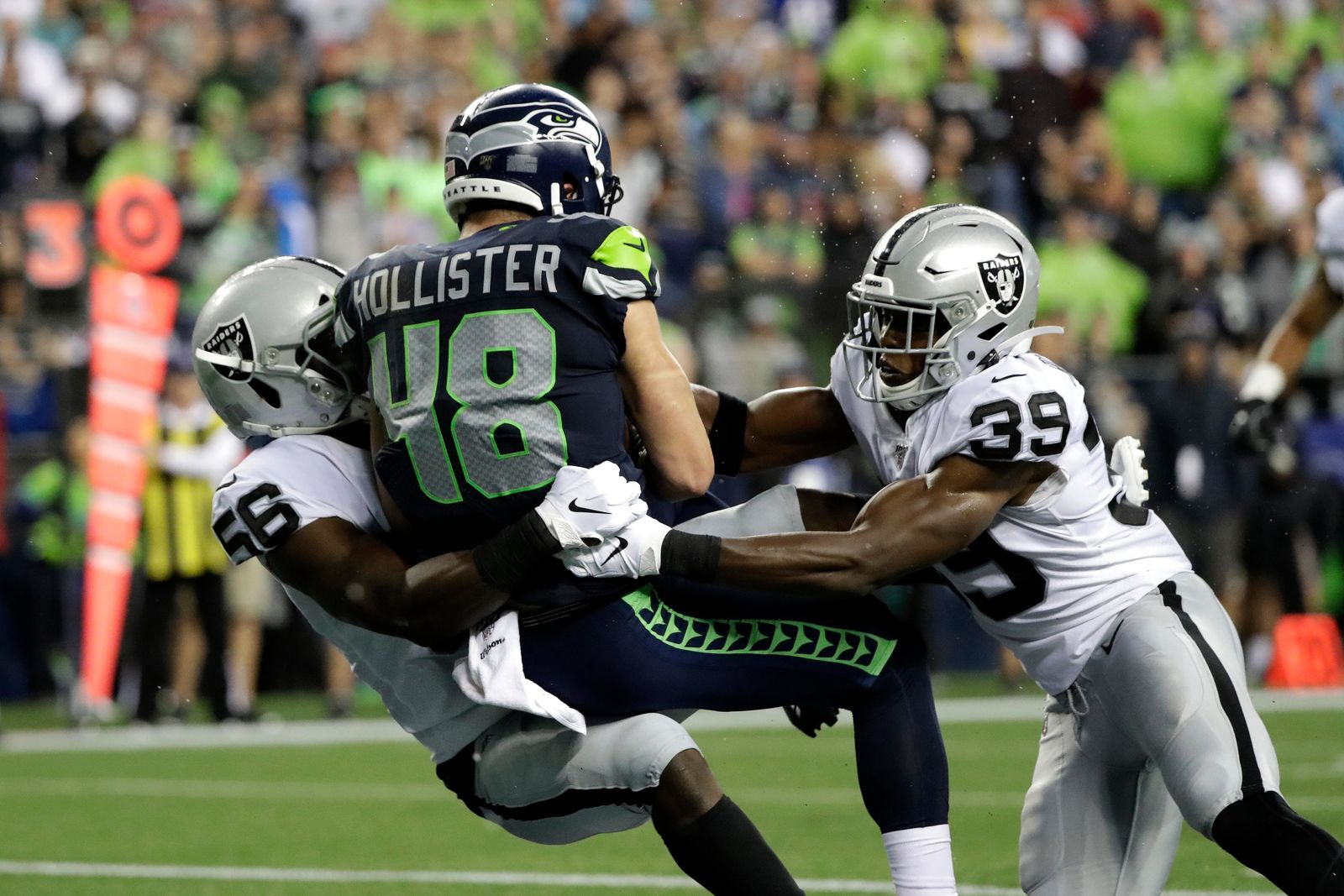 Seattle Seahawks tight end Jacob Hollister (48) scores a touchdown after a reception as he is tackled by Oakland Raiders' Te'Von Coney, left, and Jordan Richards, right, during the first half of an NFL football preseason game Thursday, Aug. 29, 2019, in Seattle. (AP Photo/Elaine Thompson)