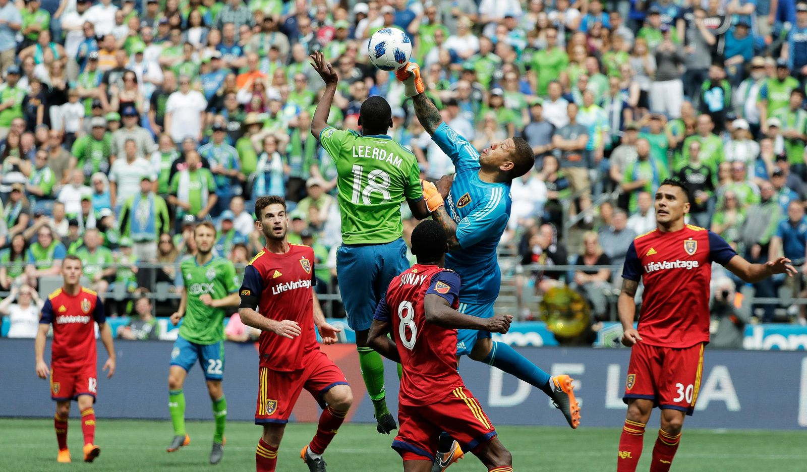 Real Salt Lake goalkeeper Nick Rimando, second from right, punches the ball away from Seattle Sounders defender Kelvin Leerdam (18) during the second half of an MLS soccer match Saturday, May 26, 2018, in Seattle. Real Salt Lake won 1-0. (AP Photo/Ted S. Warren)