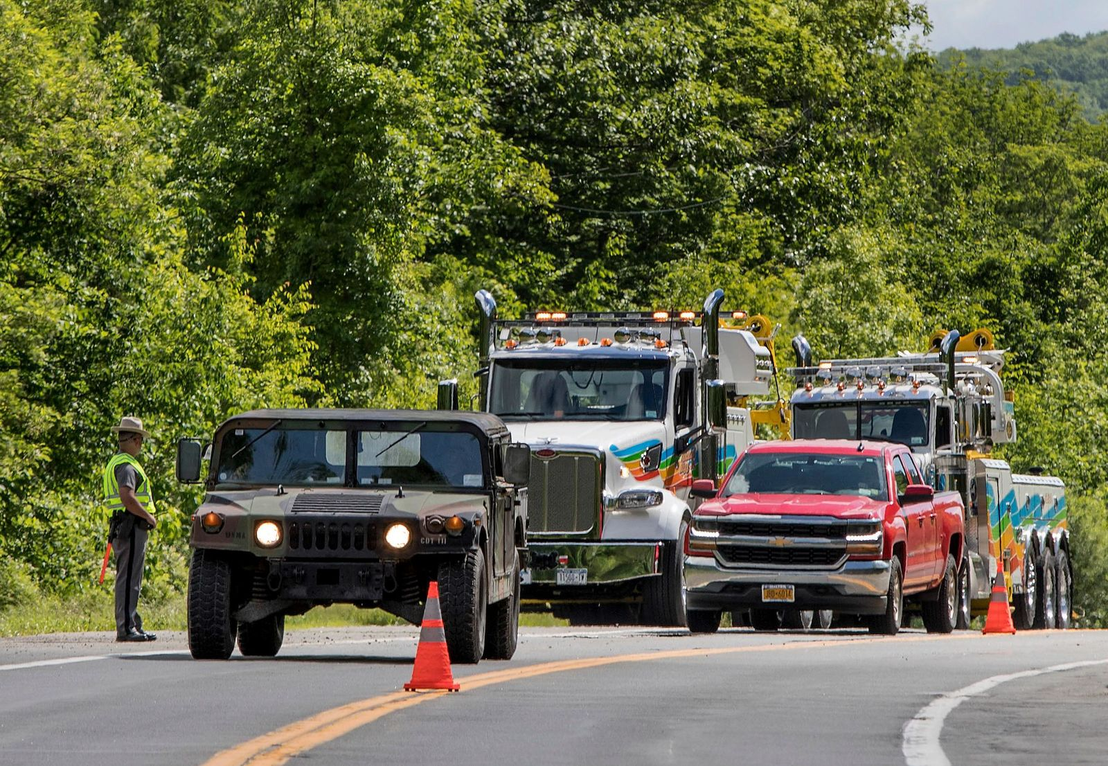 Military police direct traffic along Route 293 near the site where an armored personnel vehicle overturned killing at least one person, Thursday, June 6, 2019, in Cornwall, N.Y. (AP Photo/Allyse Pulliam)