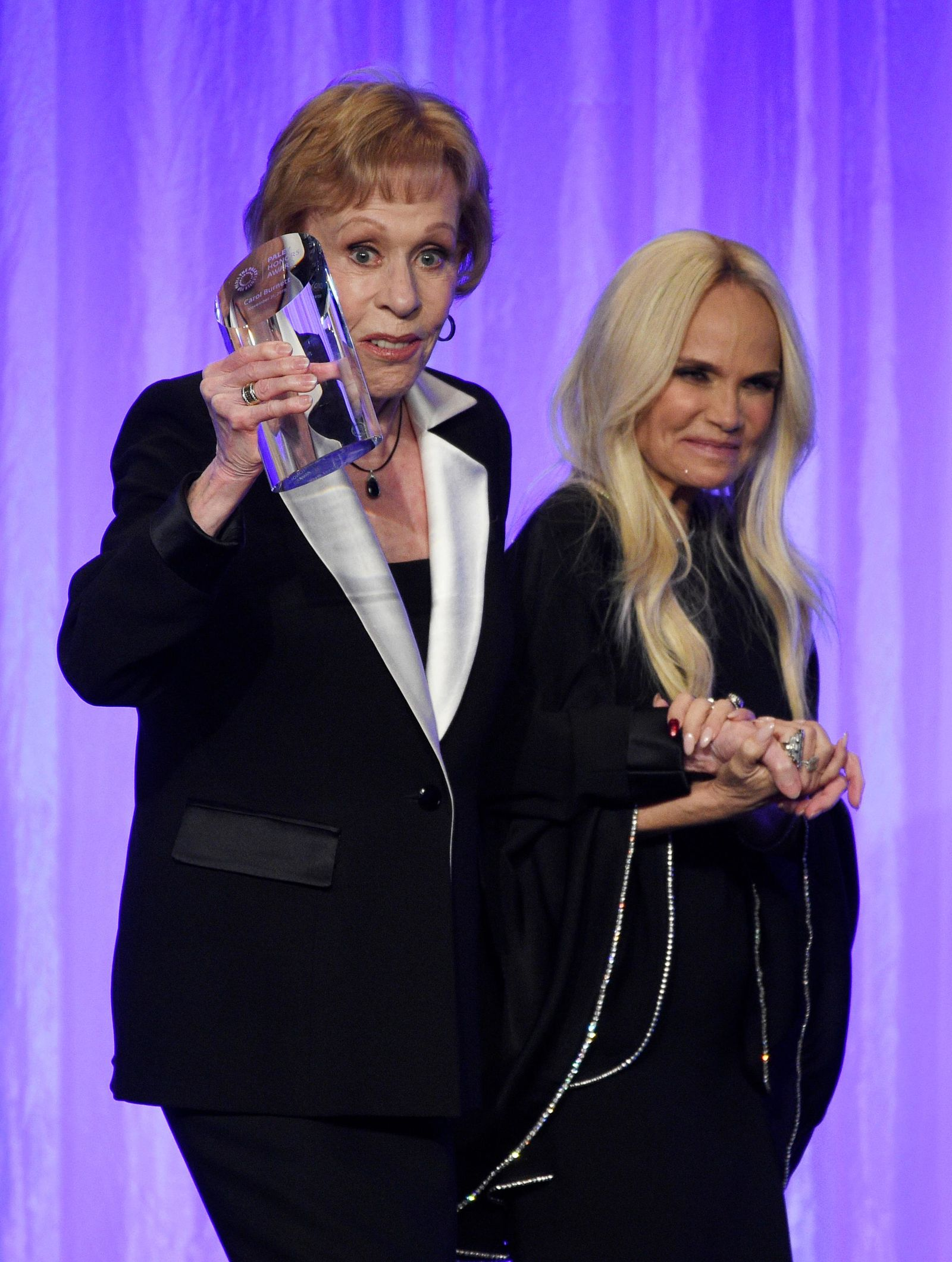 "Honoree Carol Burnett, left, is led offstage by presenter Kristin Chenoweth during ""The Paley Honors: A Special Tribute to Television's Comedy Legends"" at the Beverly Wilshire Hotel, Thursday, Nov. 21, 2019, in Beverly Hills, Calif. (Photo by Chris Pizzello/Invision/AP)"