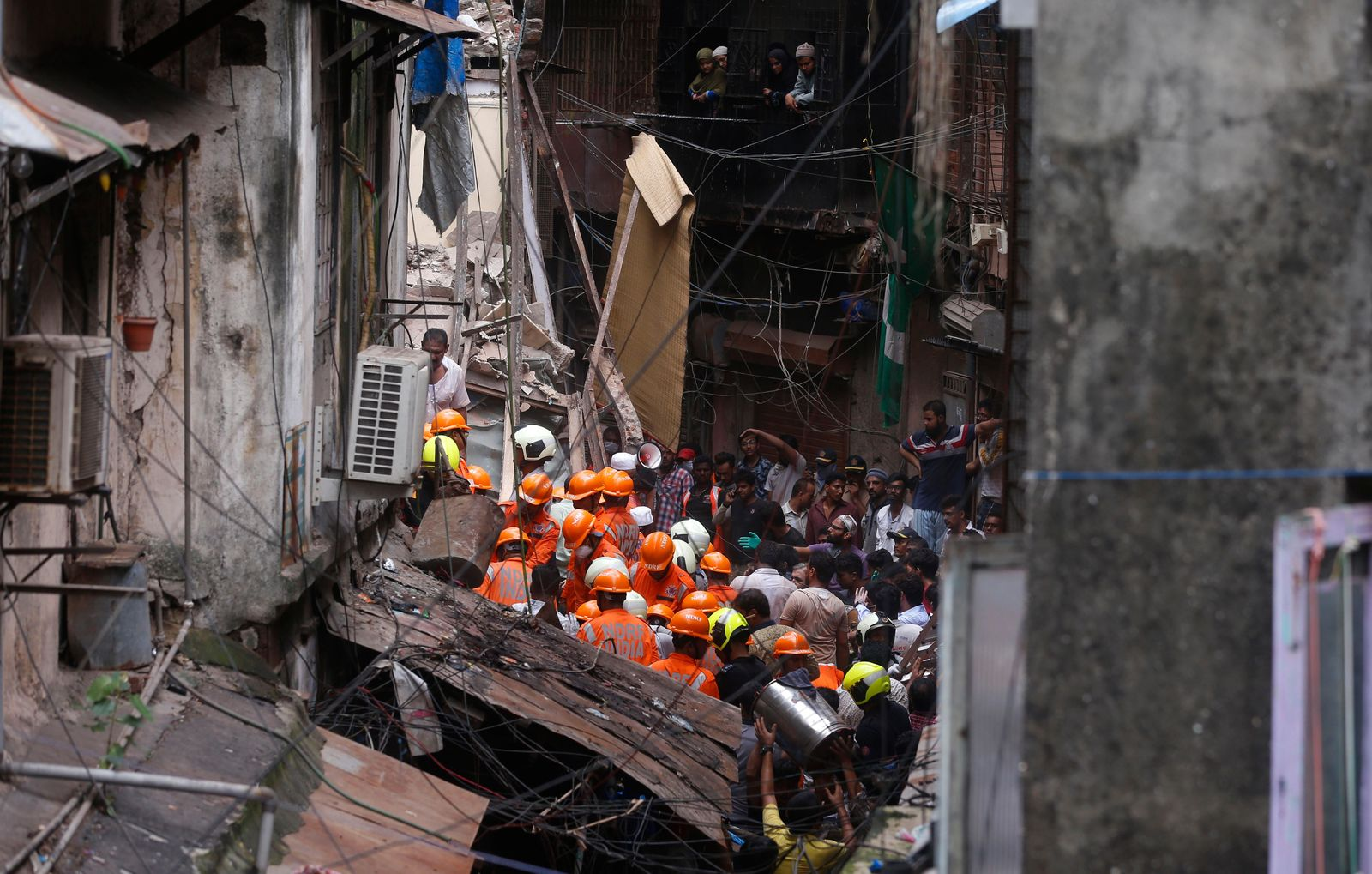 Rescuers work at the site of a building that collapsed in Mumbai, India, Tuesday, July 16, 2019. A four-story residential building collapsed Tuesday in a crowded neighborhood in Mumbai, India's financial and entertainment capital, and several people were feared trapped in the rubble, an official said. (AP Photo/Rafiq Maqbool)