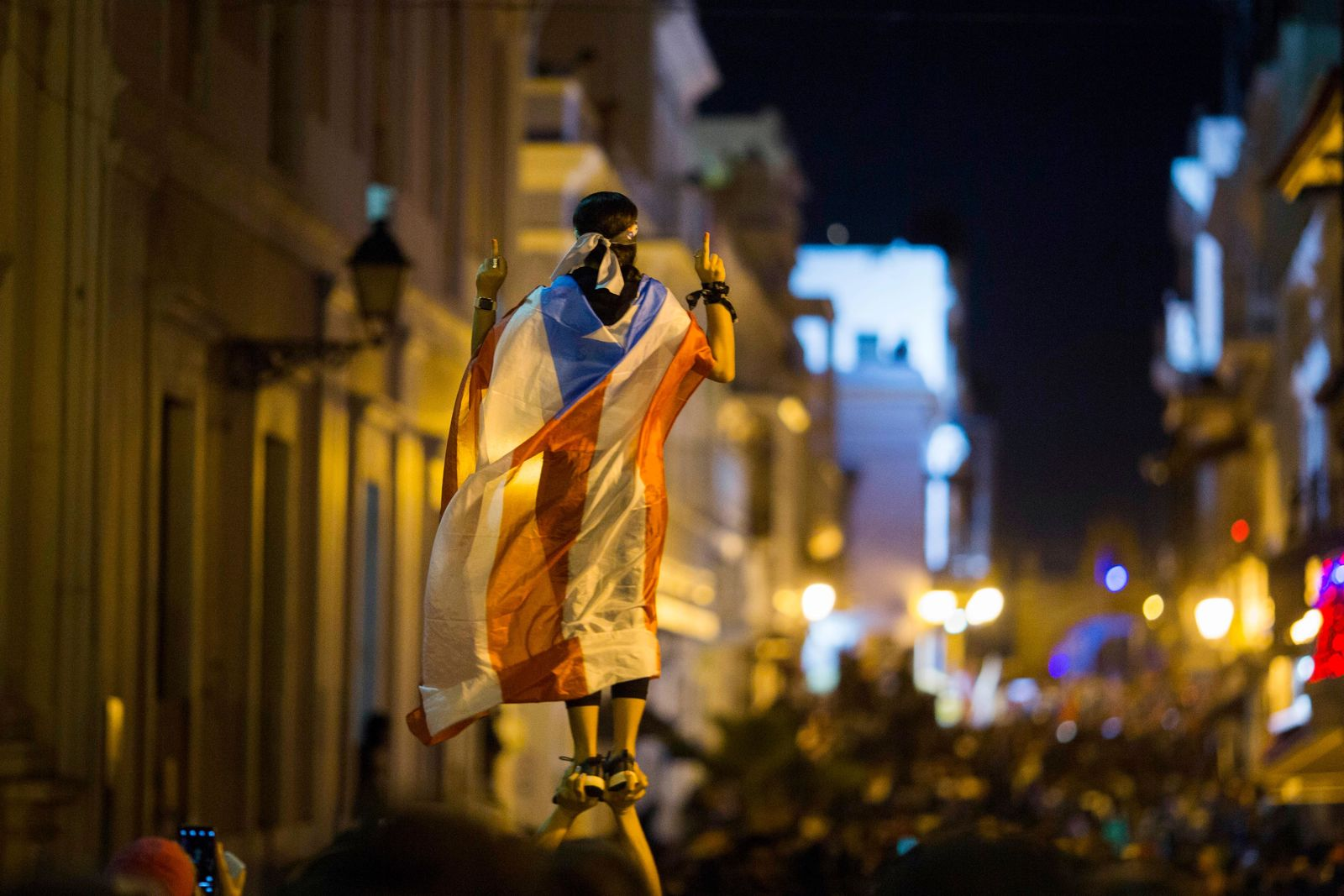 In this Wednesday, July 17, 2019 photo, a demonstrator with a Puerto Rican flag draped over his shoulders balances on the hands of another during clashes in San Juan, Puerto Rico. Thousands of people marched to the governor's residence in San Juan on Wednesday chanting demands for Gov. Ricardo Rossello to resign after the leak of online chats that show him making misogynistic slurs and mocking his constituents. (AP Photo/Dennis M. Rivera Pichardo)