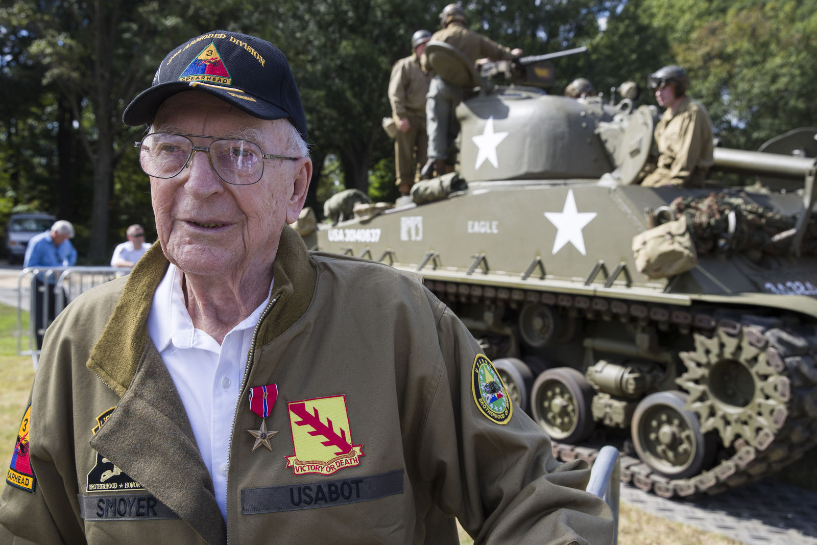World War II veteran Clarence Smoyer, 96, poses for a picture in front of a Sherman tank after receiving the Bronze Star, near the World War II Memorial, Wednesday, Sept. 18, 2019, in Washington. Smoyer fought with the U.S. Army's 3rd Armored Division, nicknamed the Spearhead Division. In 1945, he defeated a German Panther tank near the cathedral in Cologne, Germany — a dramatic duel filmed by an Army cameraman that was seen all over the world. (AP Photo/Alex Brandon)