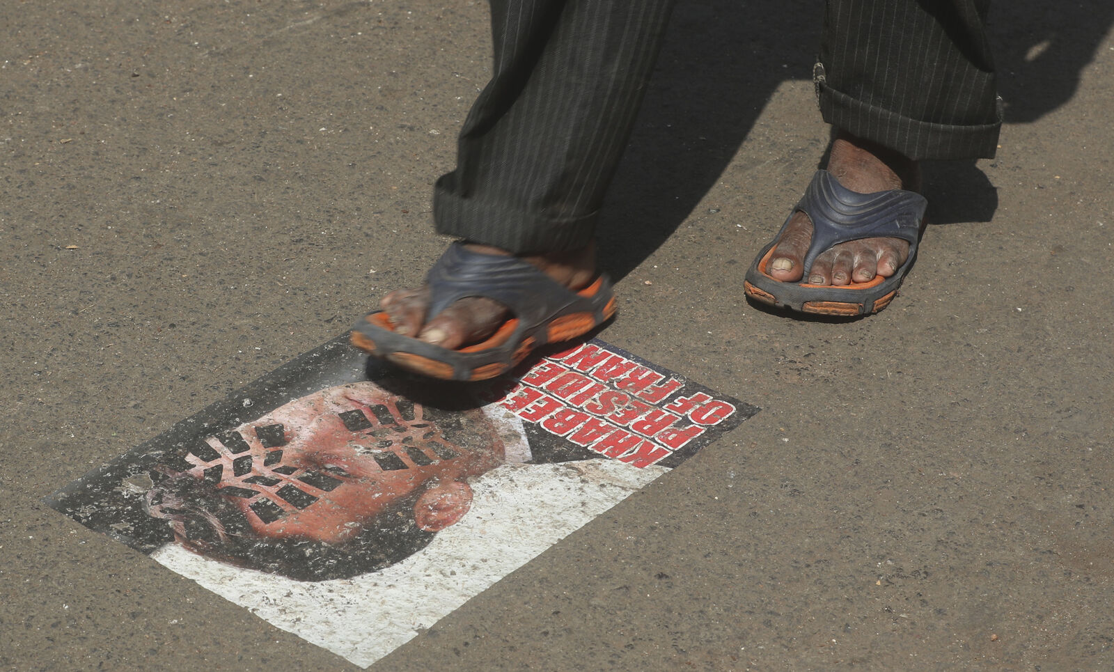 A man walks on a defaced image of French President Emmanuel Macron pasted on a street in Mumbai, India, Friday, Oct. 30, 2020. (AP Photo/Rafiq Maqbool)