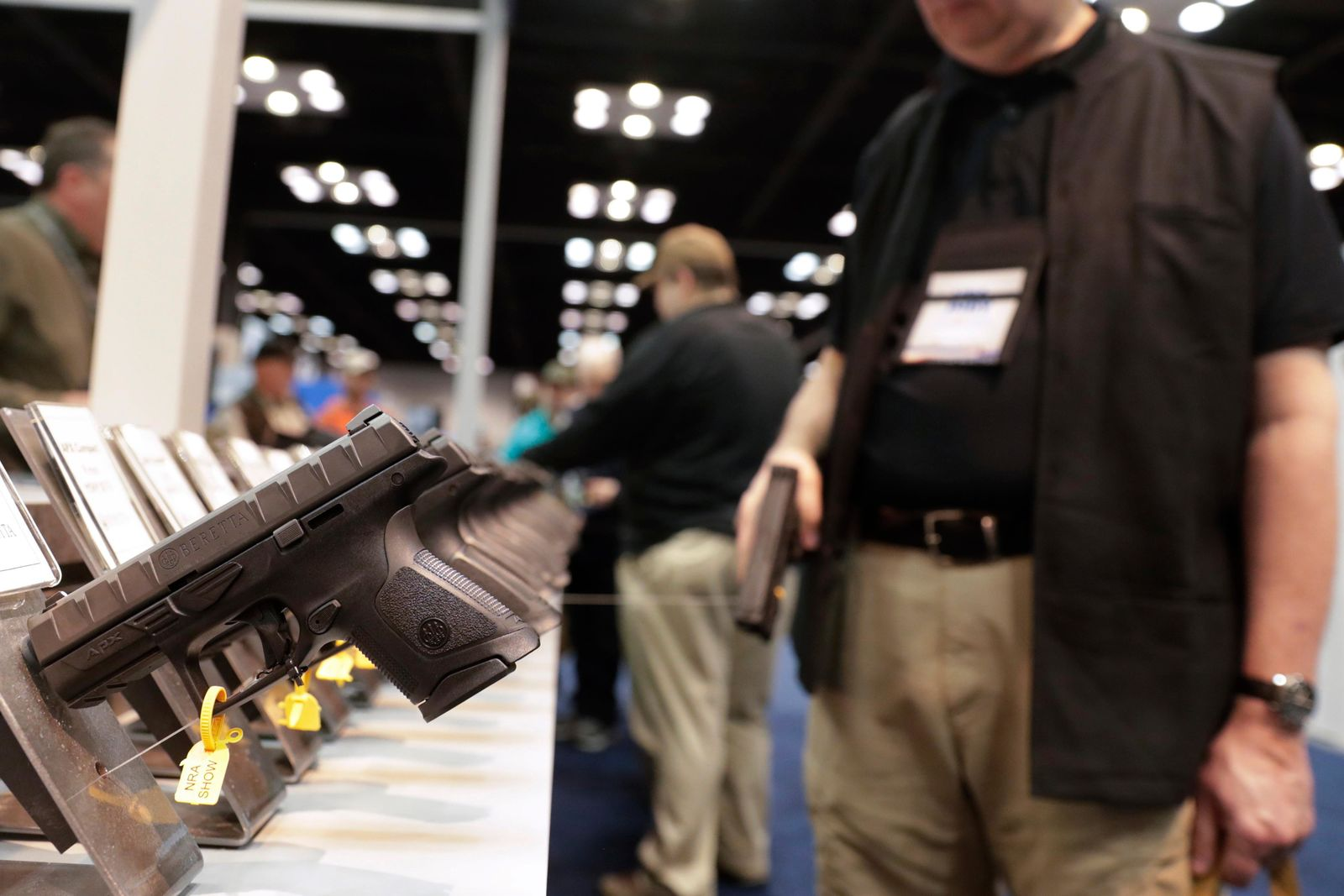 FILE - In this April 27, 2019, file photo, a gun enthusiast looks over the display of pistols in the exhibition hall at the National Rifle Association annual meeting in Indianapolis. (AP Photo/Michael Conroy, File)