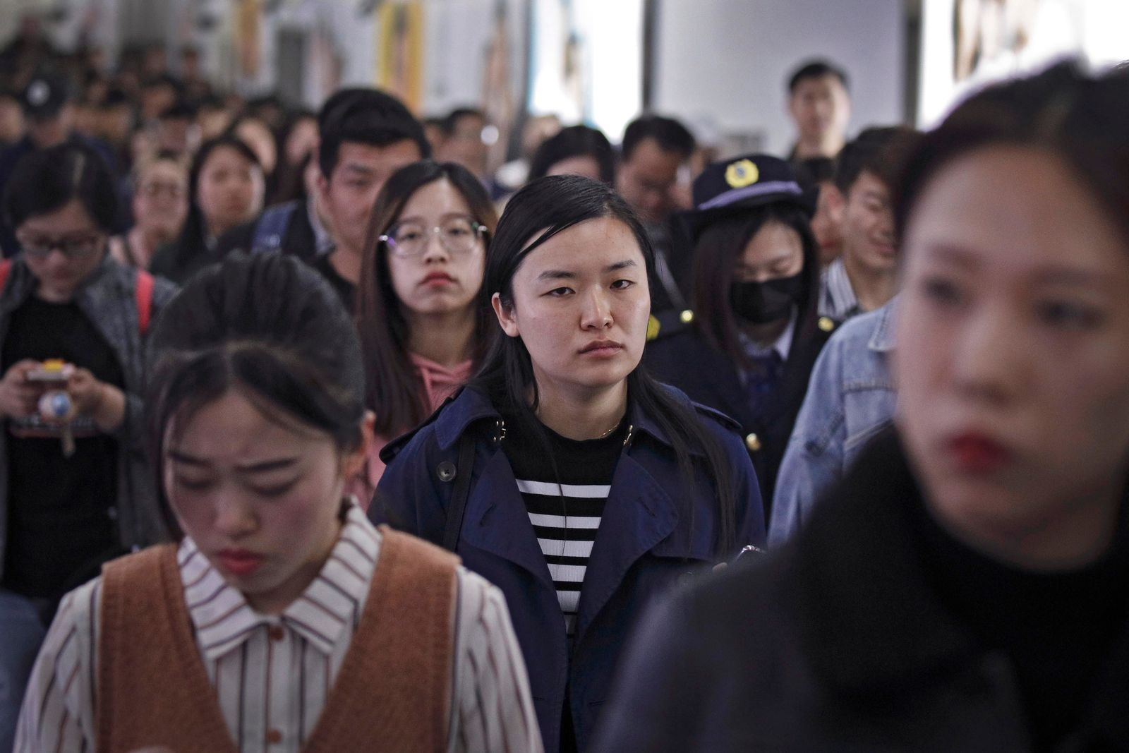 In this Wednesday, April 17, 2019, photo, Young Chinese people walk inside a subway station during the evening rush hour in Beijing.{ } (AP Photo/Andy Wong)