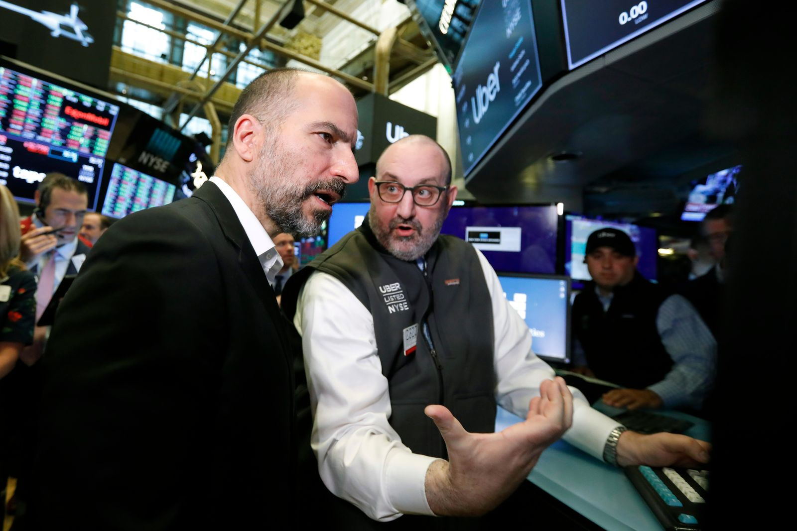 Uber CEO Dara Khosrowshahi, left, talks with specialist Peter Giacchi before his stock begins trading at the New York Stock Exchange, as his company makes its initial public offering, Friday, May 10, 2019. (AP Photo/Richard Drew)