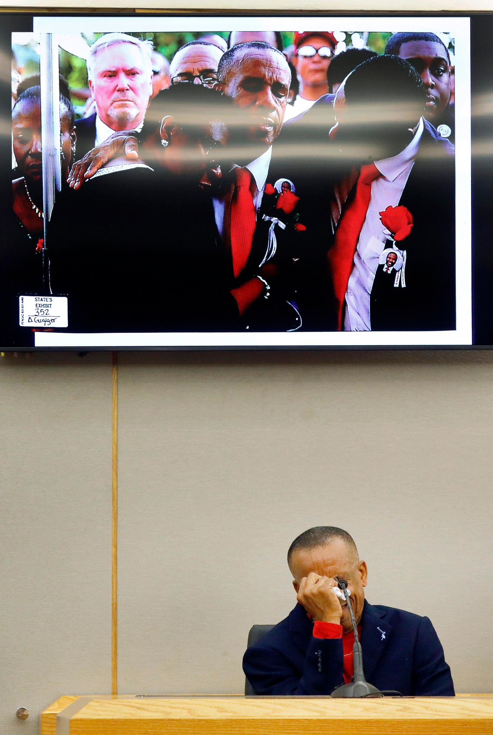 Bertrum Jean, father of Botham Jean, breaks down on the witness stand talking about the day he buried his son, pictured above, during the punishment phase of the trial of former Dallas police officer Amber Guyger, Wednesday, Oct. 2, 2019 at the Frank Crowley Courts Building in Dallas.  Guyger was convicted of murder Tuesday in the killing of Botham Jean and faces a sentence that could range from five years to life in prison or be lowered to as little as two years if the jury decides the shooting was a crime of sudden passion. (Tom Fox/The Dallas Morning News via AP, Pool)